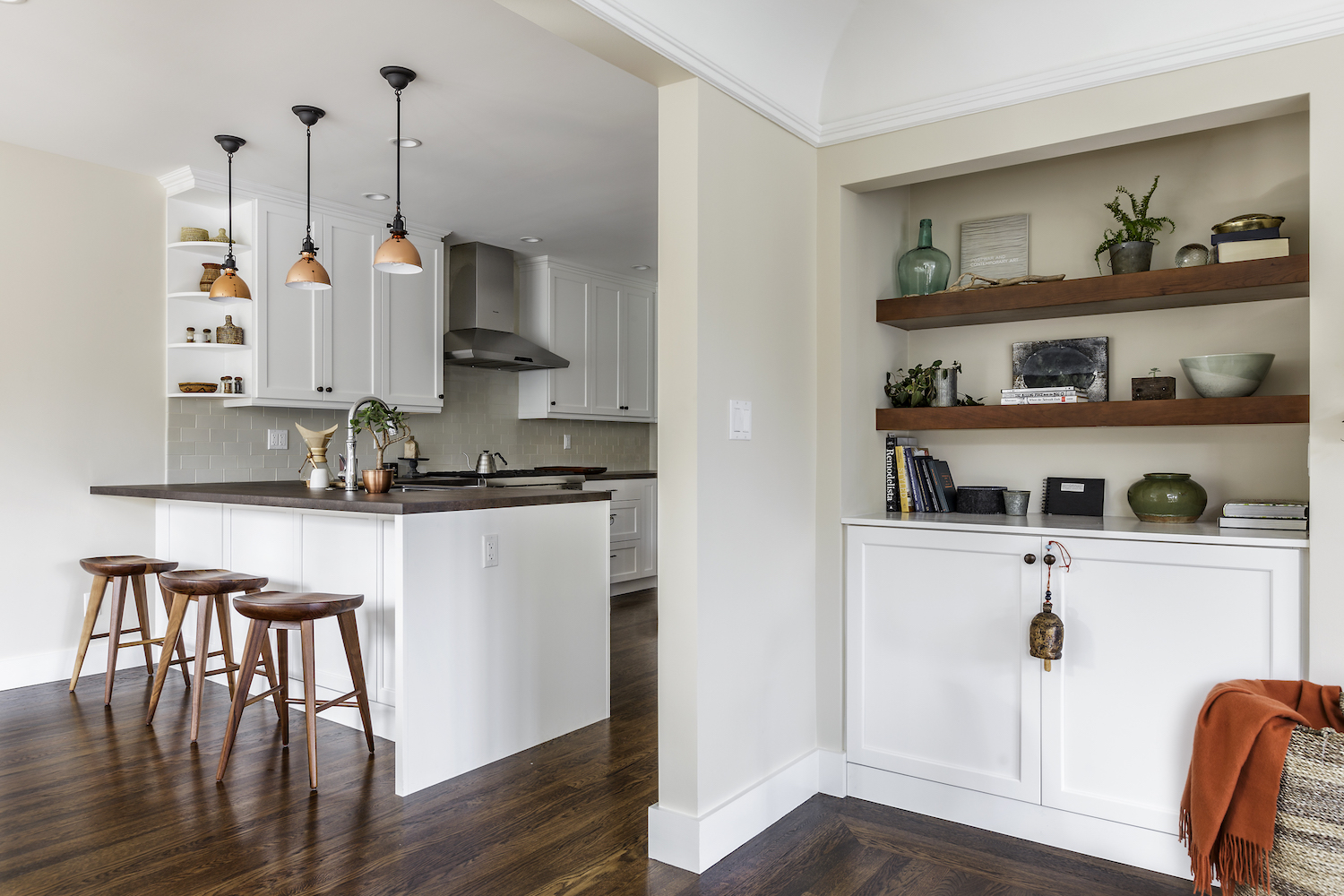 kitchen with white cabinets and stainless steel appliances and pendant lighting and bar seating.jpg