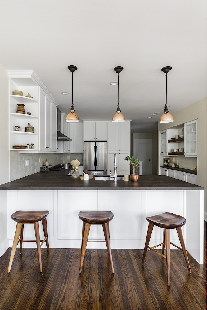 kitchen with bar seating and white cabinets and wood flooring and dark counters.png