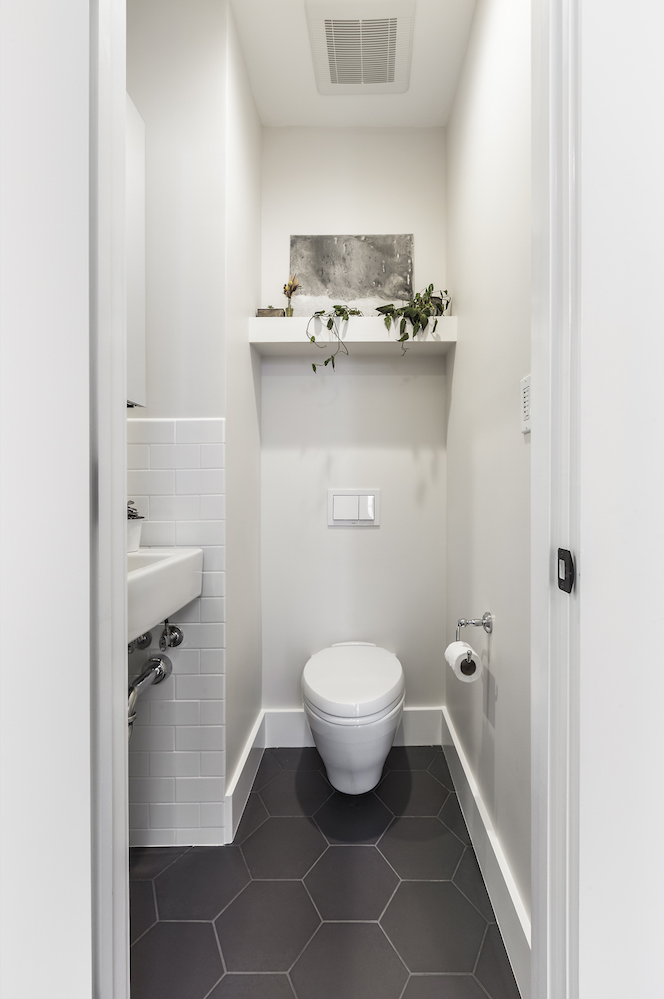 powder room with grey hexagon floor tile and floor mounted toilet and decorative shelving.png