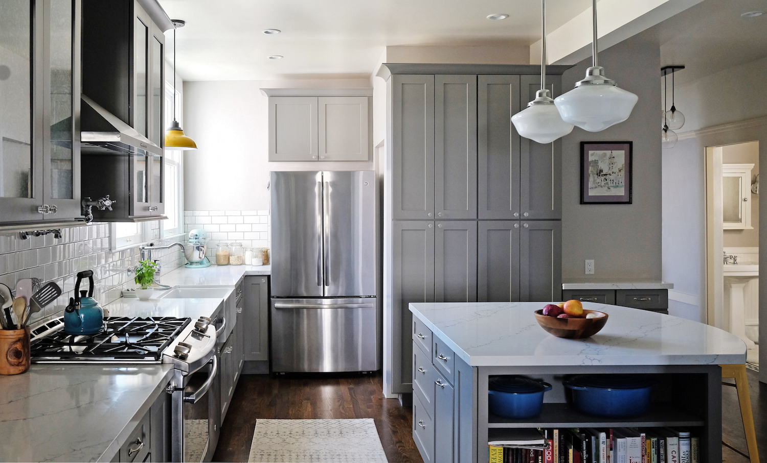 grey and white kitchen with wood flooring and stainless steel appliances.jpg