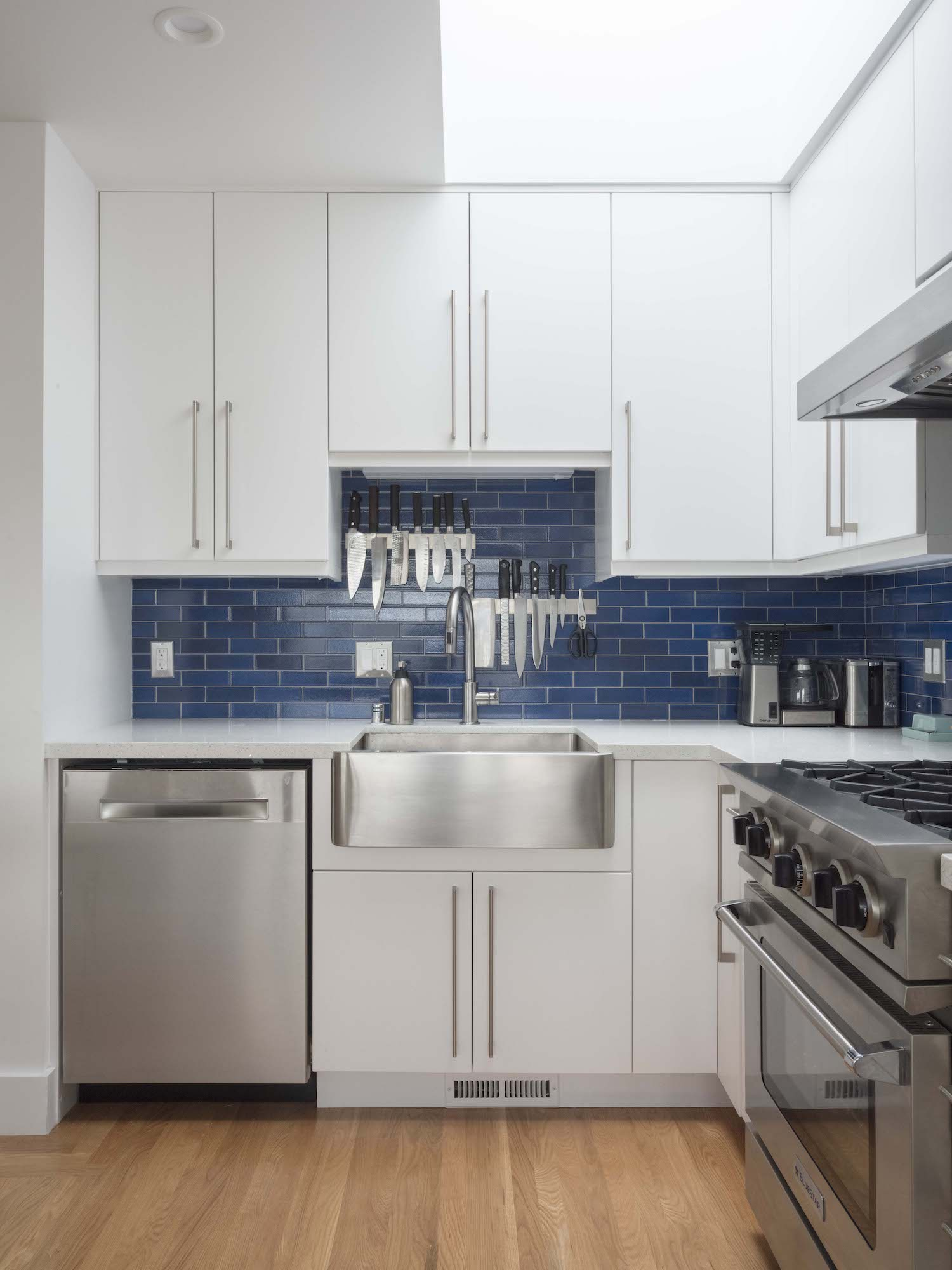 kitchen with white cabinets and blue tile backsplash and stainless steel appliances and brushed nickel hardware.jpg