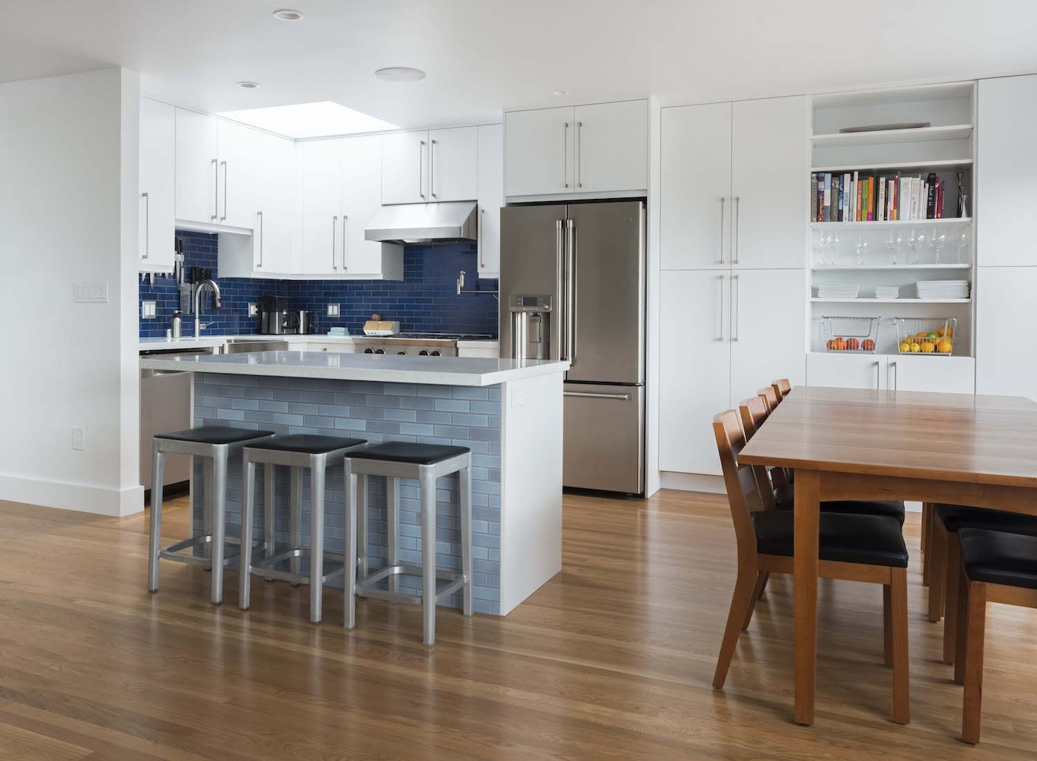 kitchen with white cabinets and wood flooring and blue tile backsplash and stainless steel appliances and wooden dining table.jpg