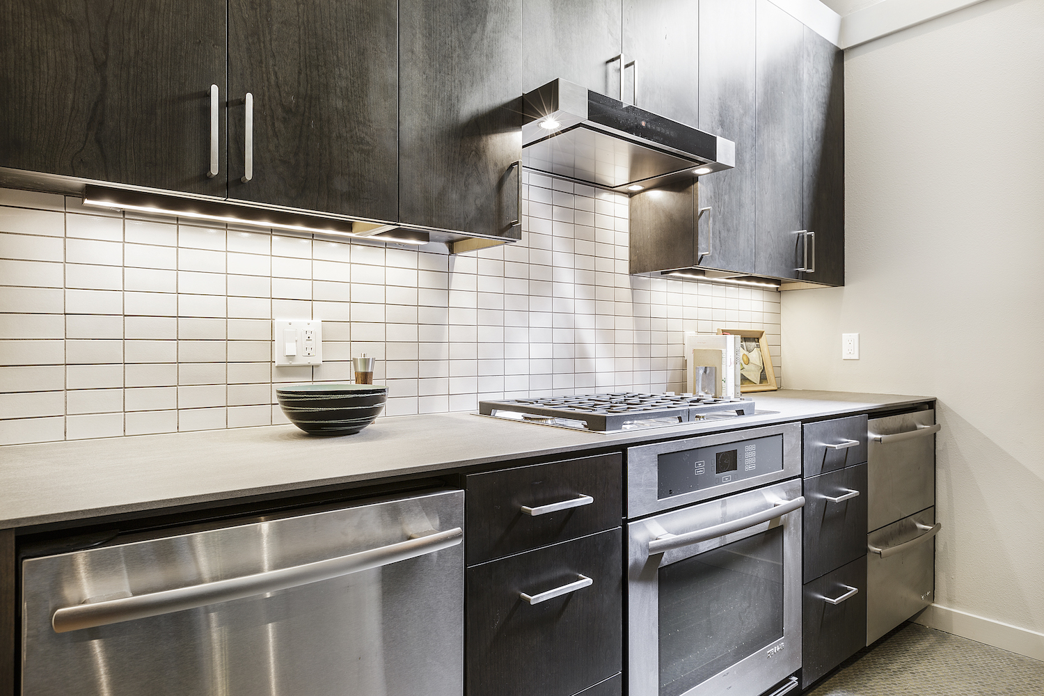 kitchen with dark wood cabinets and under cabinet lighting and stainless steel appliances and brushed nickel cabinet hardware and white tile backsplash.jpg