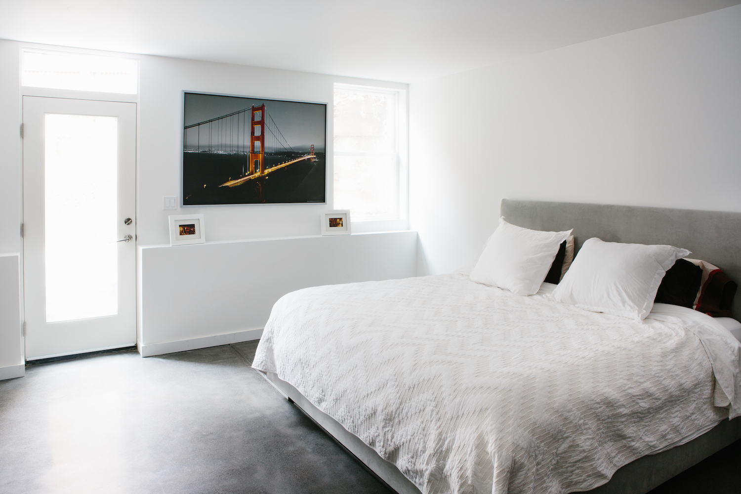 bedroom with cement floors and white walls and decorative ledge and grey fabric bed grame.jpg
