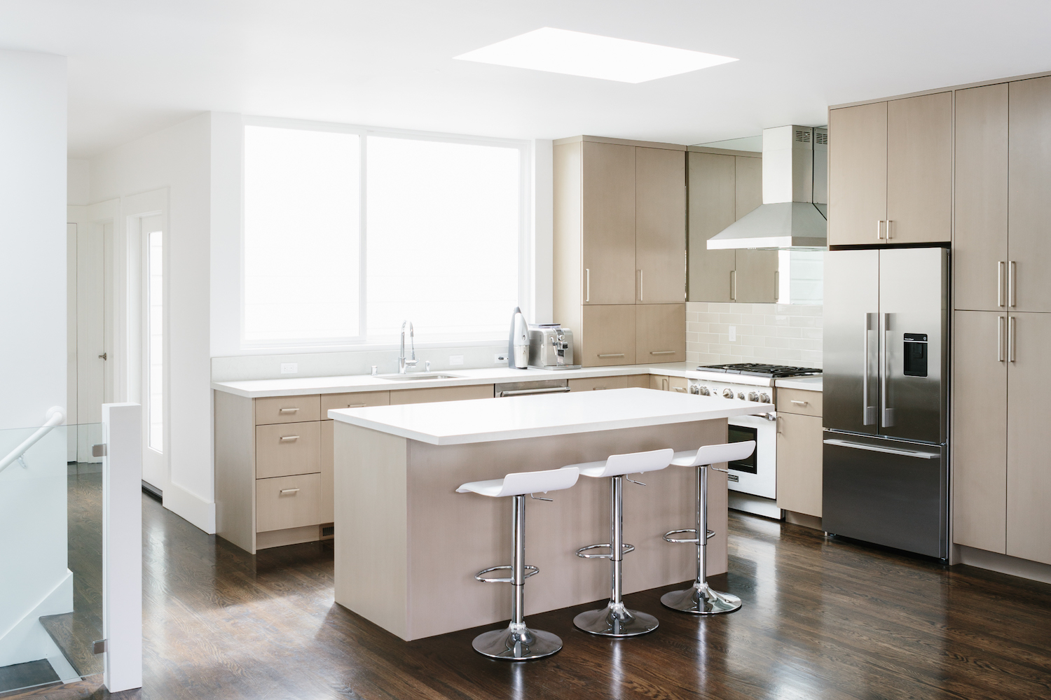 kitchen with light wood cabinets and center island and bar seating and white counters and stainless steel appliances.jpg
