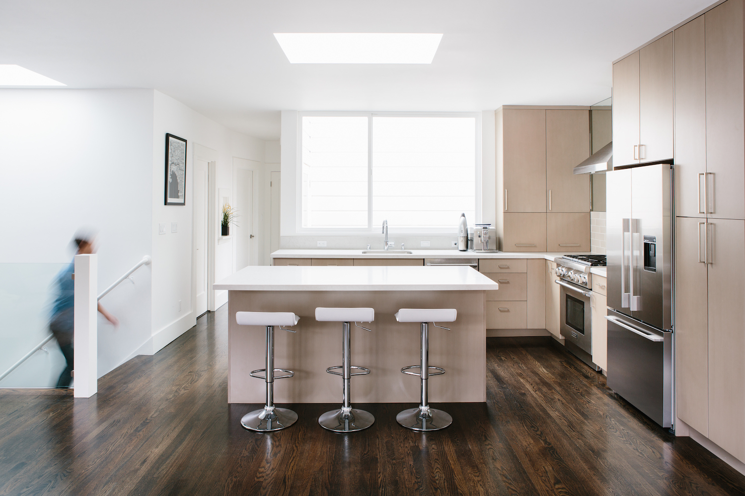 kitchen with light wood cabinets and wood flooring and center island and white counters and bar seating and chrome fixtures.jpg