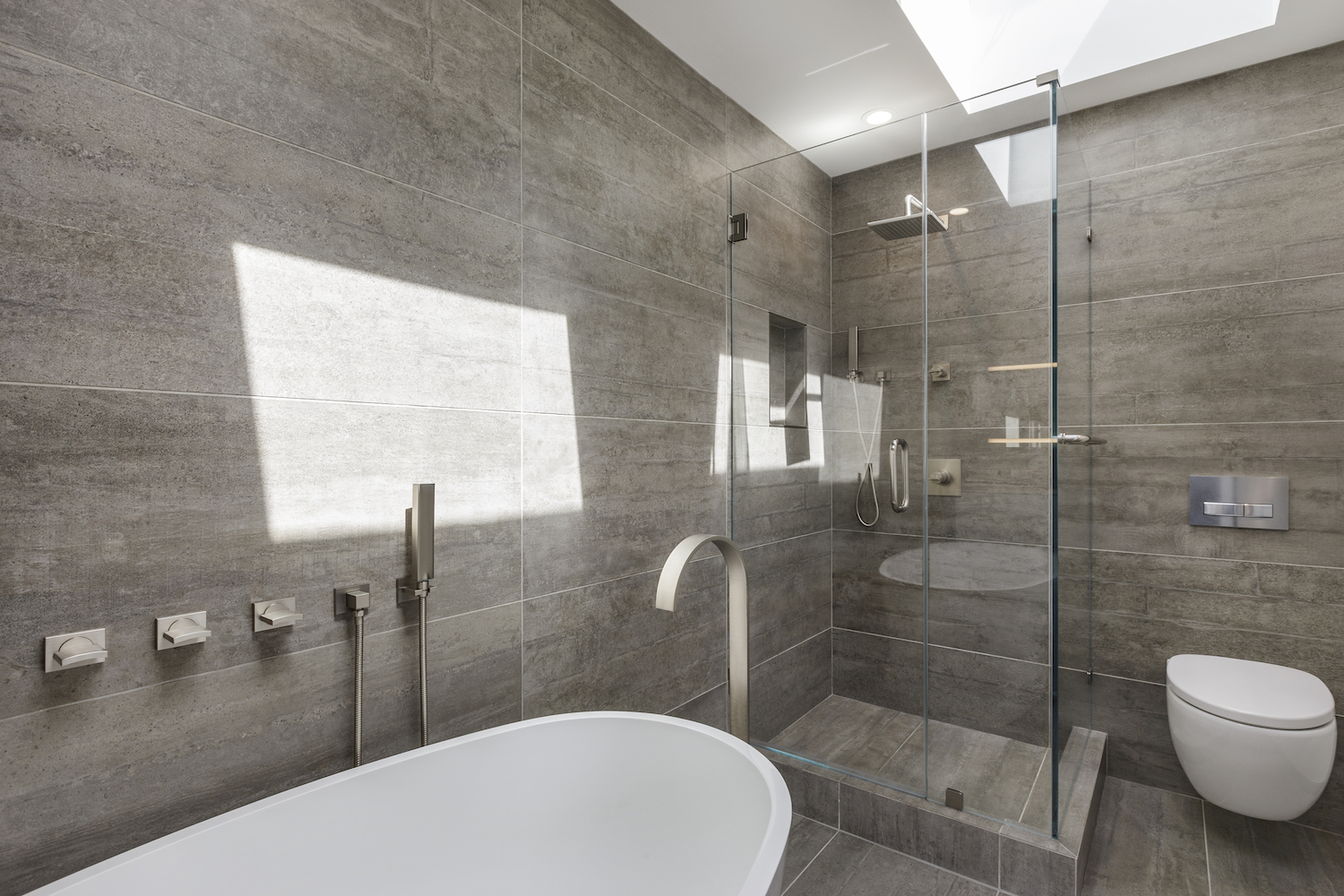 bathroom with grey wall tile and stall shower and soaking tub and wall mounted toilet and brushed nickel fixtures.jpg
