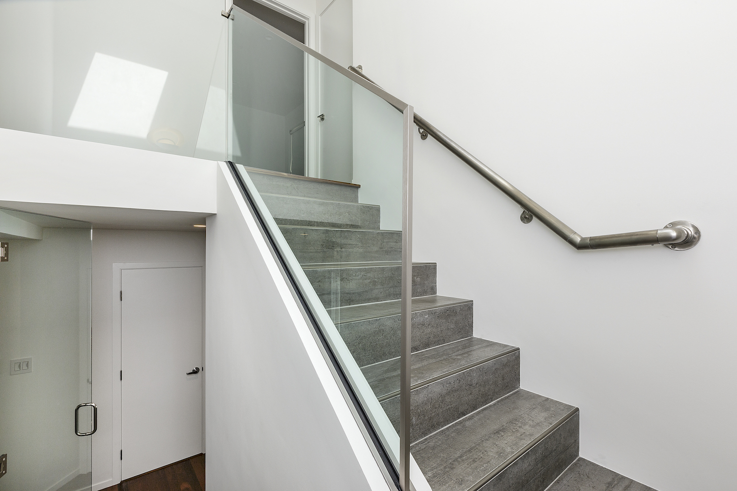 grey tile staircase with glass railing and white walls.jpg