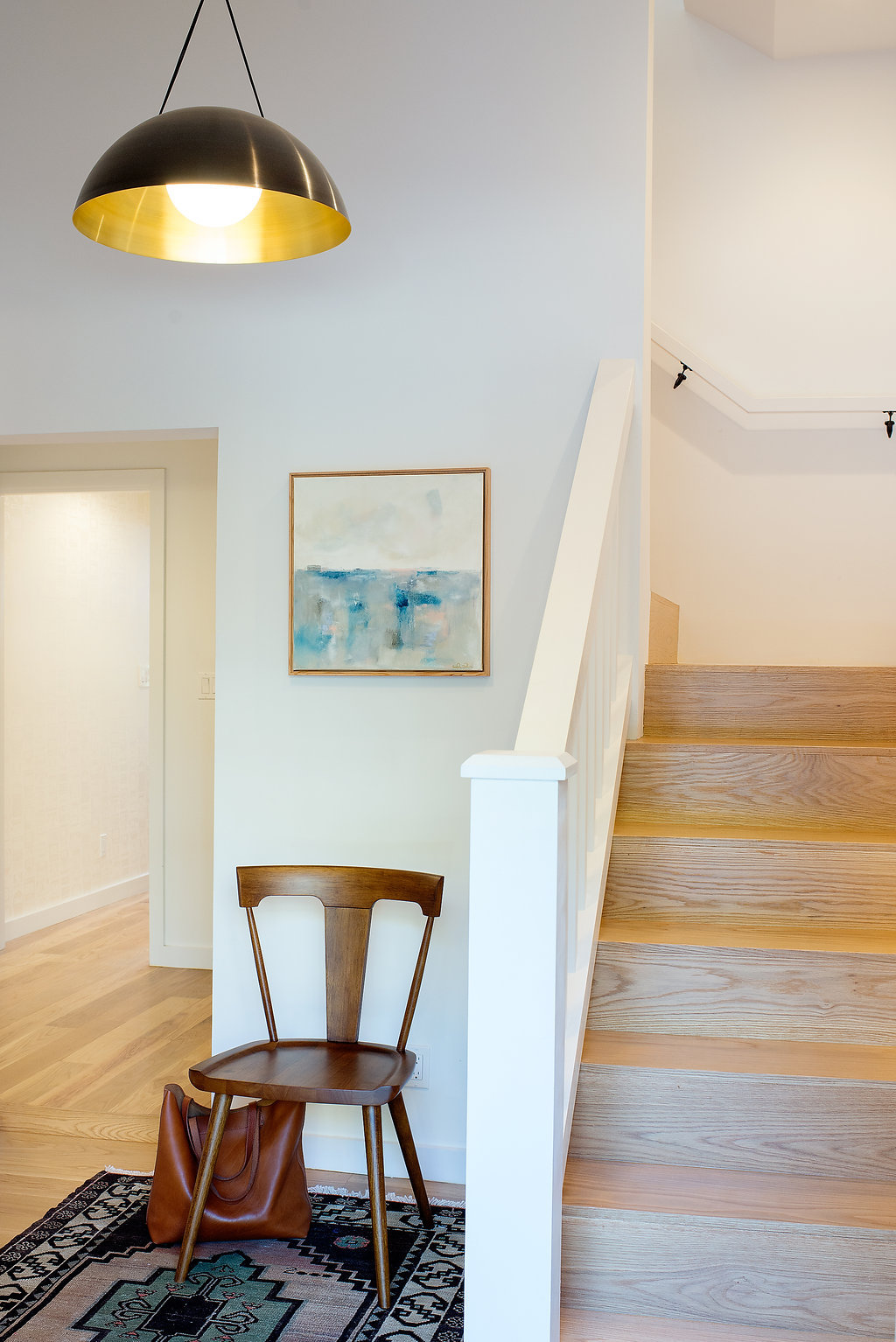wooden staircase with white railing and entry sitting area with wood chair .jpg
