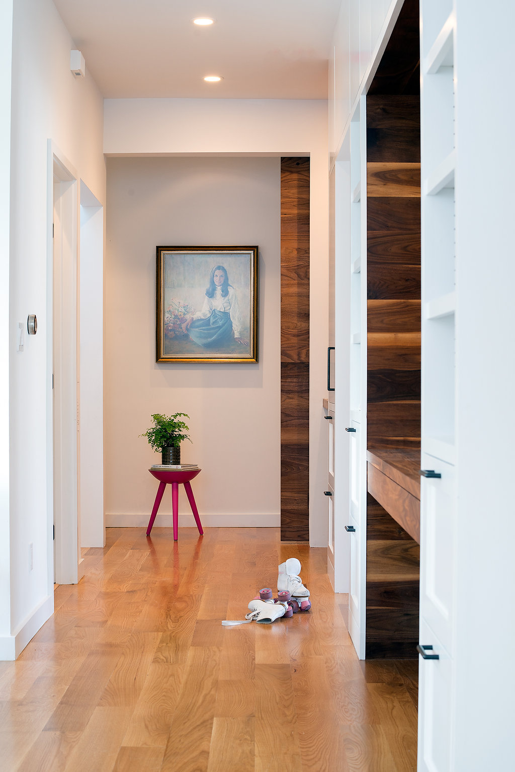 hallway with custom desk area and open shelving and drawers and wood flooirng and red accent table.jpg