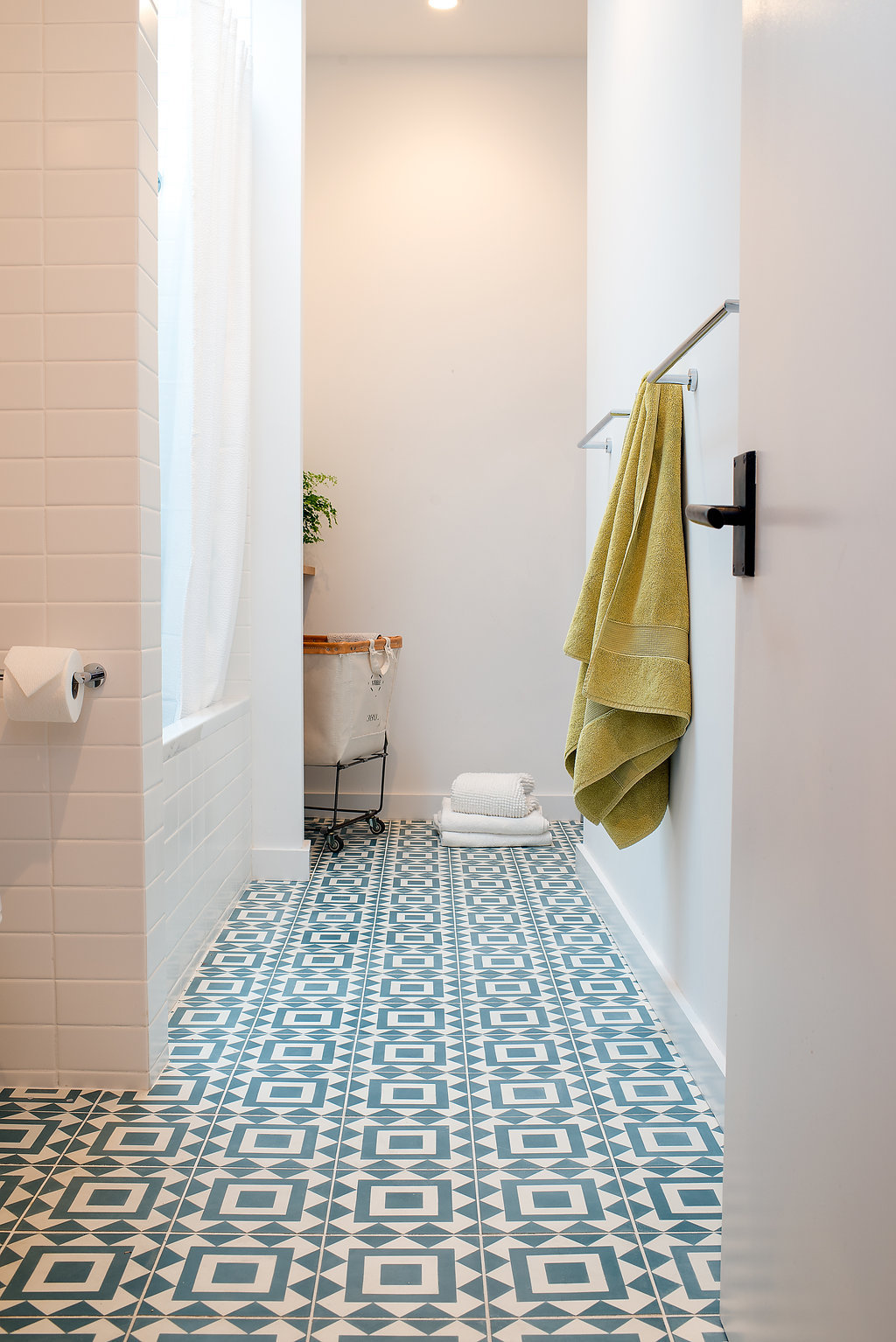 bathroom with white wall tile and blue and white patterned floor tile and chrome hardware.jpg