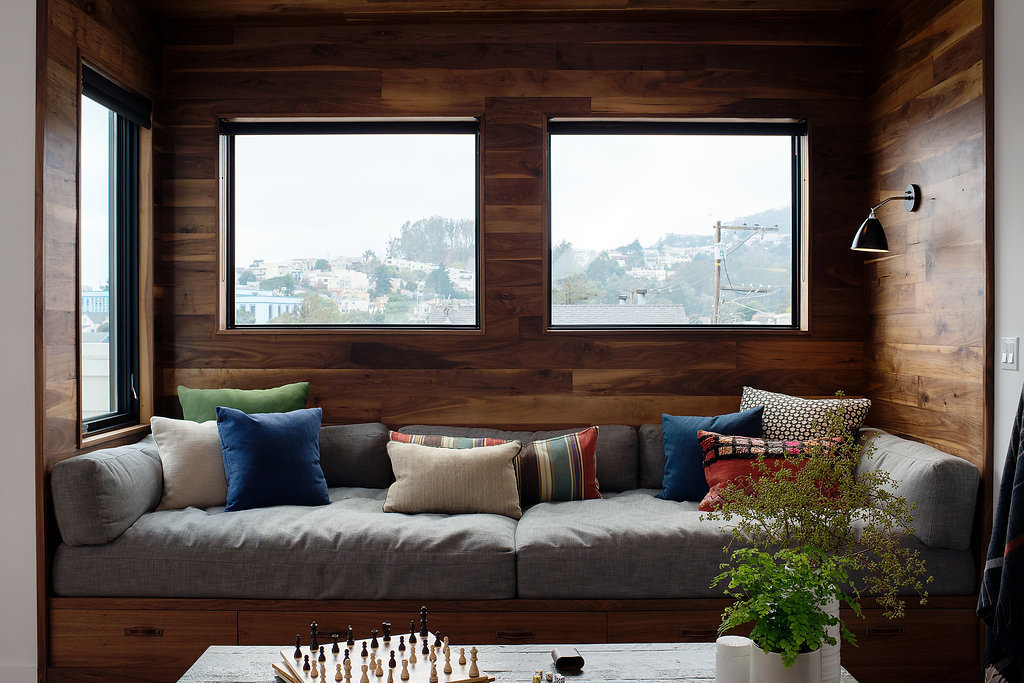custom built in seating with storage and windows and black accent lighting and grey cushions with colorful pillows.jpg