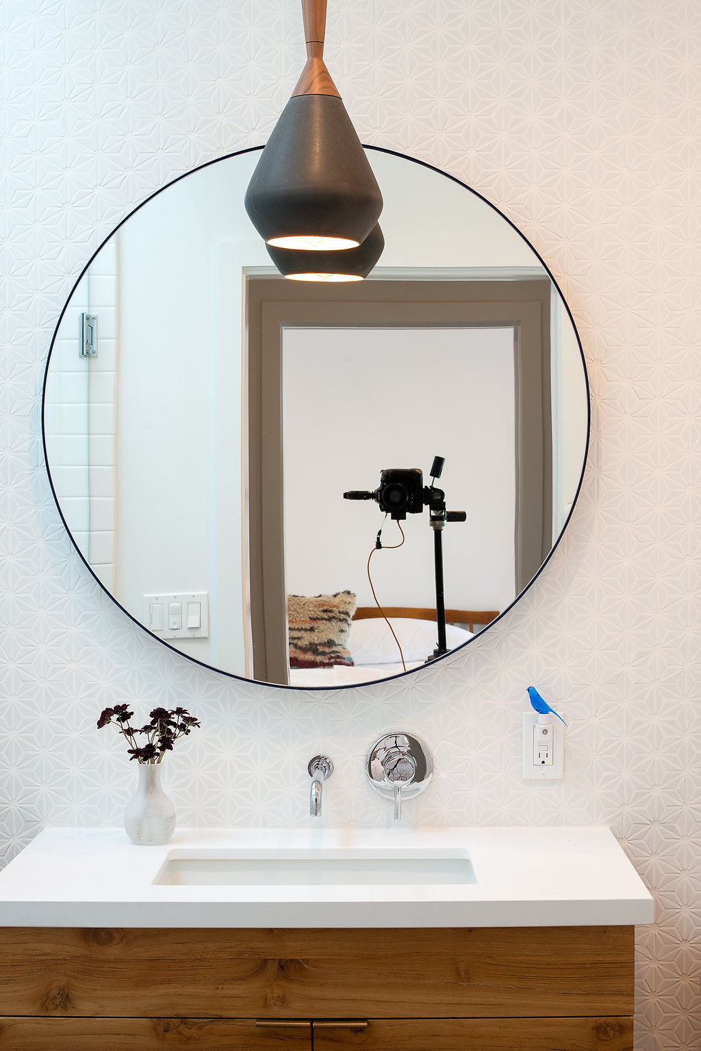 bathroom with white patterned wall and round mirror and wood vanity and white counter and chrome fixtures.jpg