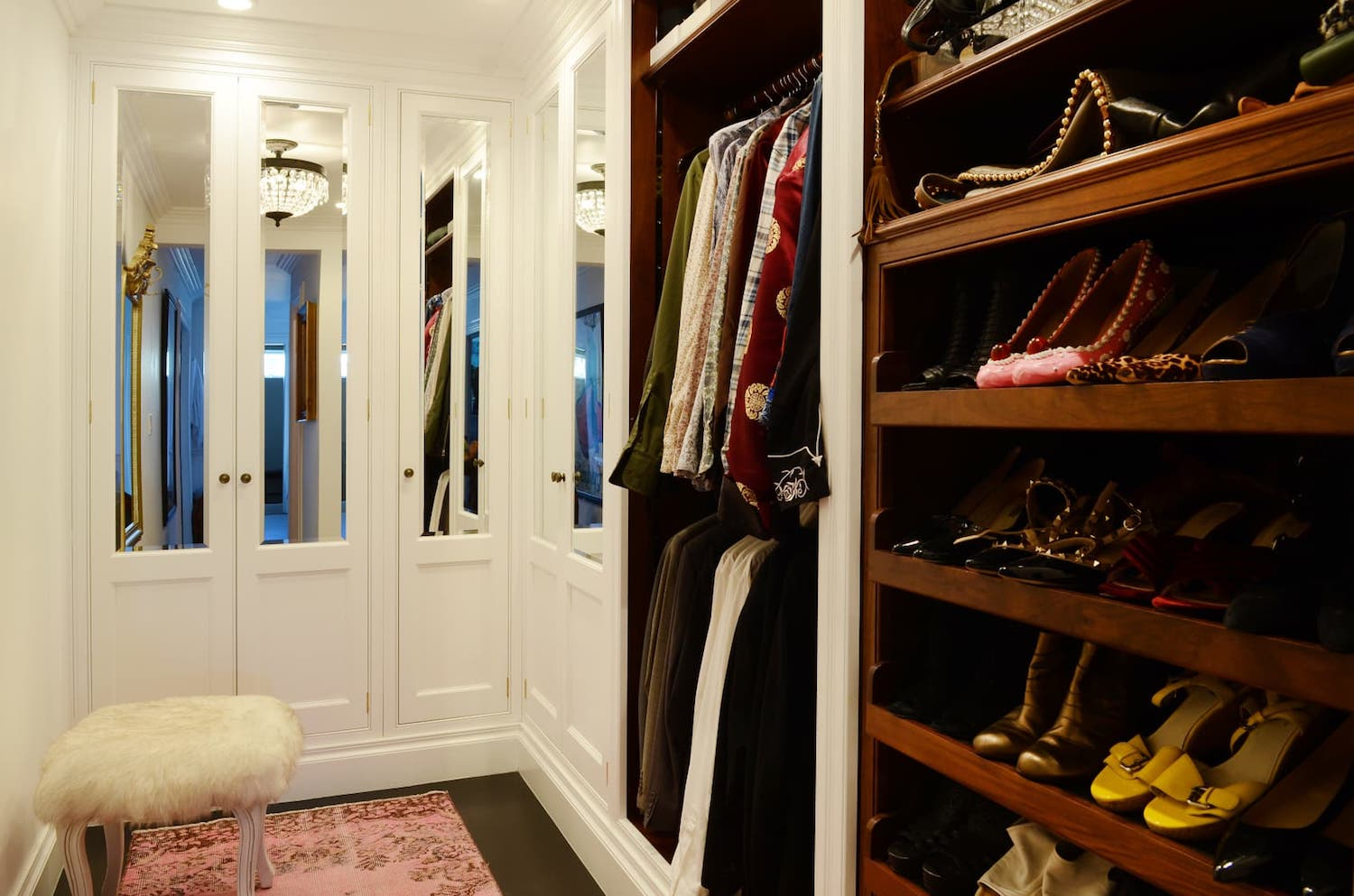 closet with open shelving and mirrored cabinets and white walls.jpeg