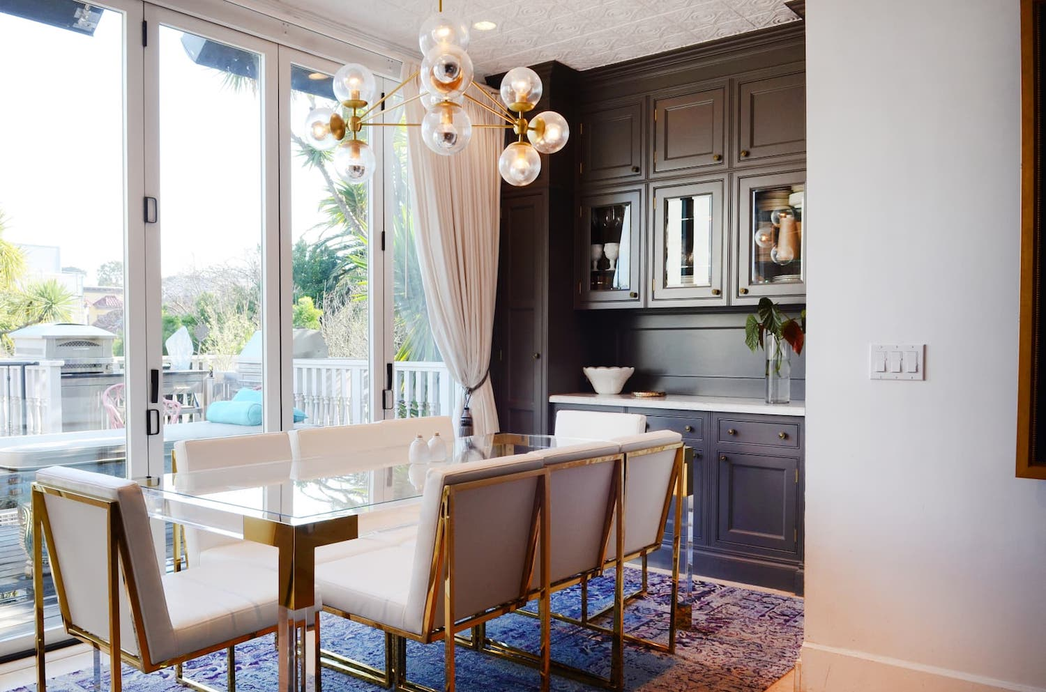 dining room with glass table and white chairs and grey cabinets and gold accents.jpeg