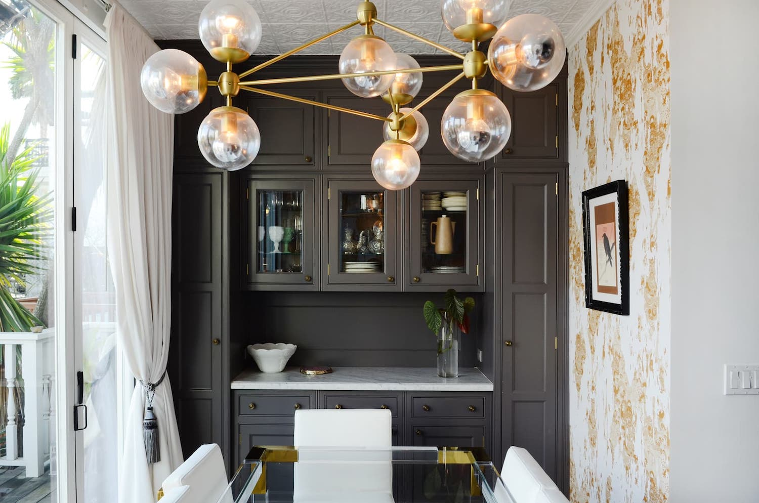 dining room with grey built ins and gold light fixture and yellow wallpaper.jpeg