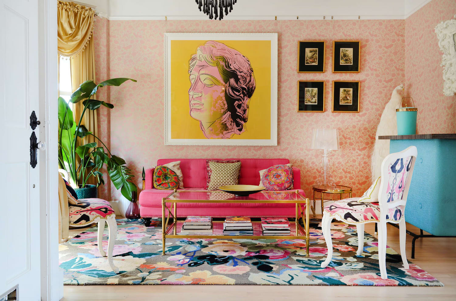 living room with bright furniture and pink wallpaper and gold accents.jpeg