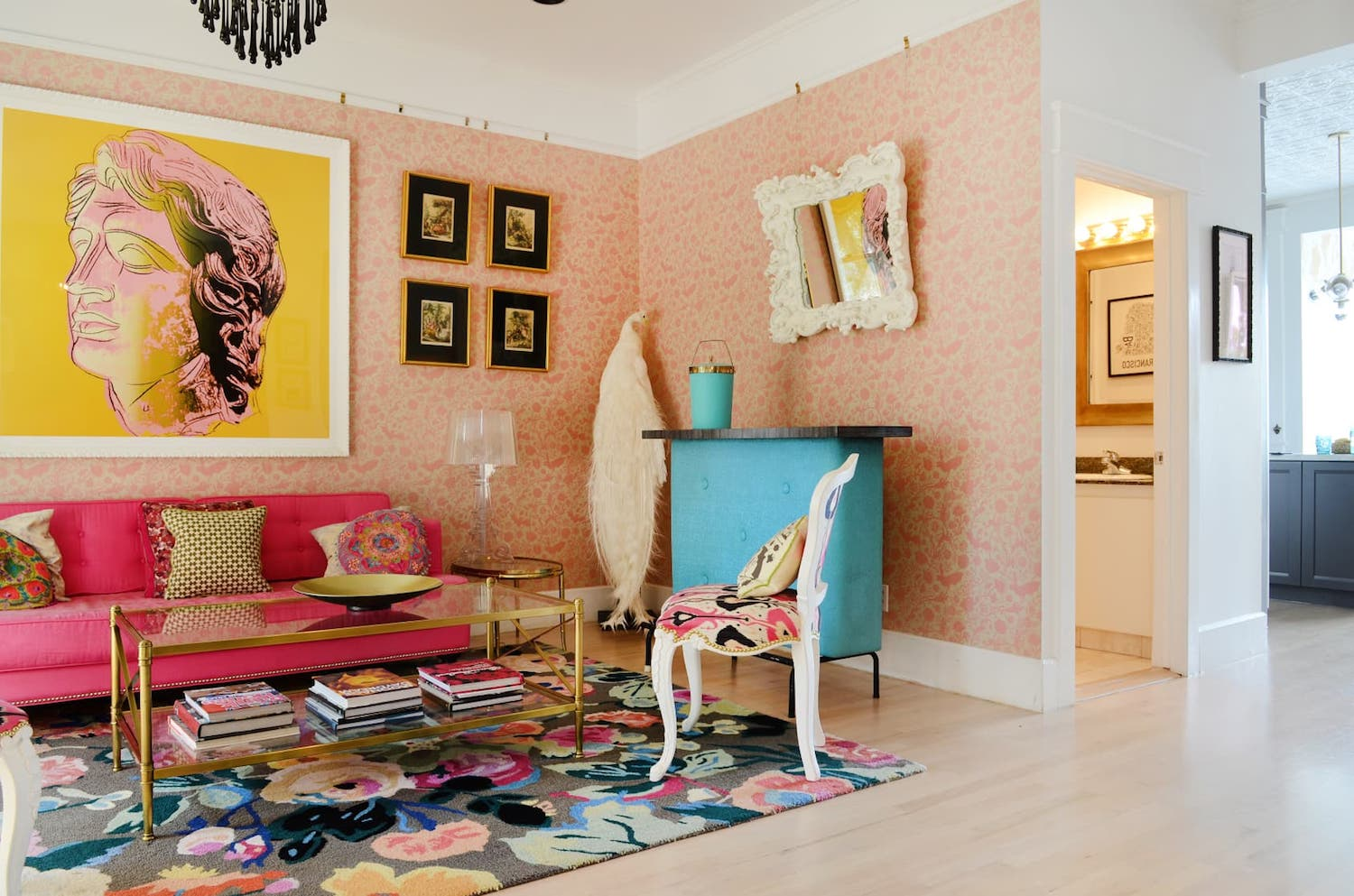 living room with pink sofa and pink wallpaper and bright art and wood floors.jpeg