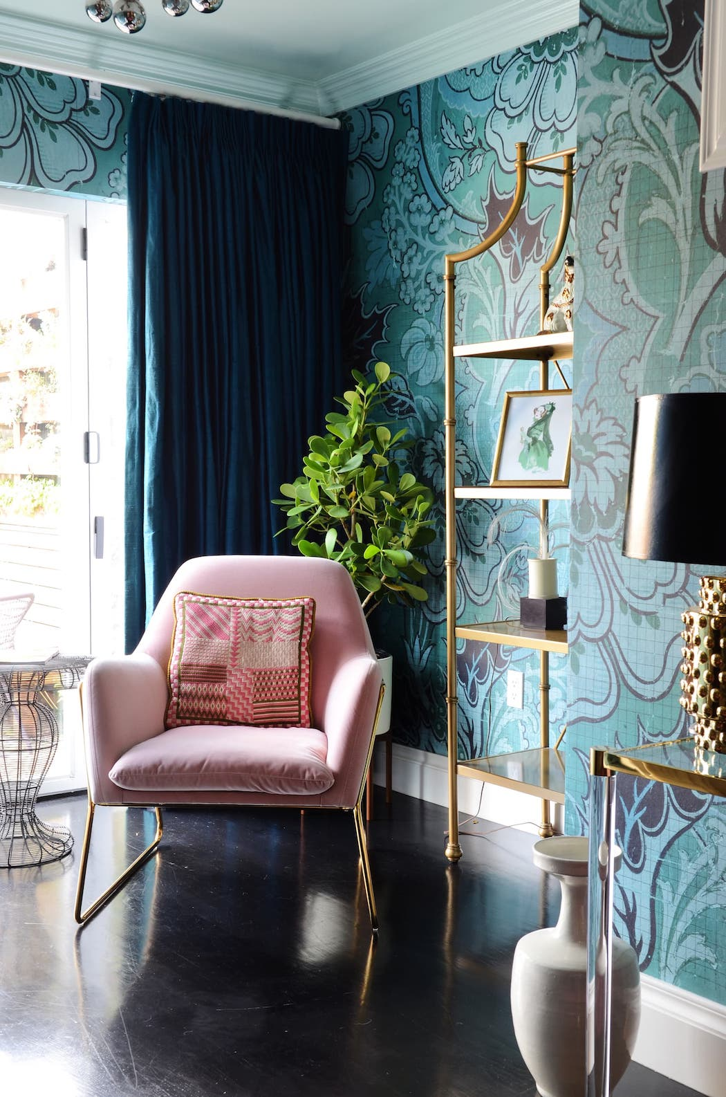 sitting area with blue wallpaper and gold accents and pink chair.jpeg