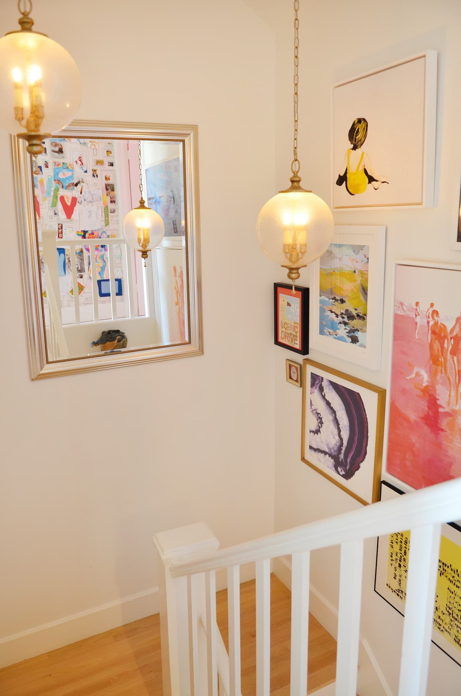 staircase with white railing and gold light fixtures and bright wall art.jpeg