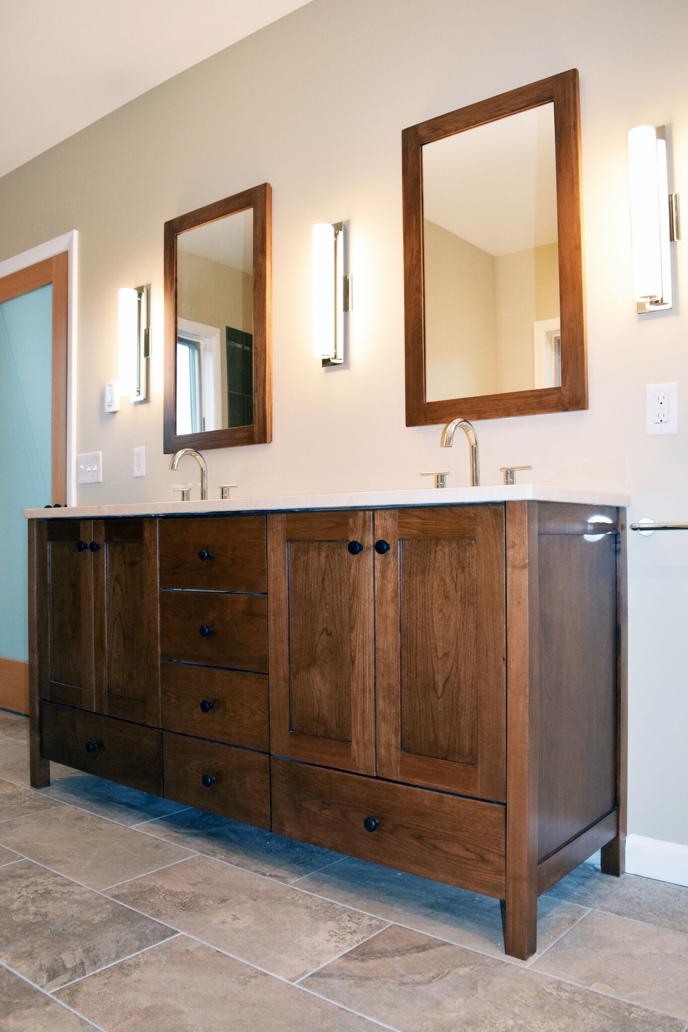 Photo of custom bathroom design. Shaker style and flush inset custom cabinets. Pull-out drawers with decorative handles. Custom cherry cabinetry. Ideas for custom cabinets and vanity designs, remodels, and renovations.