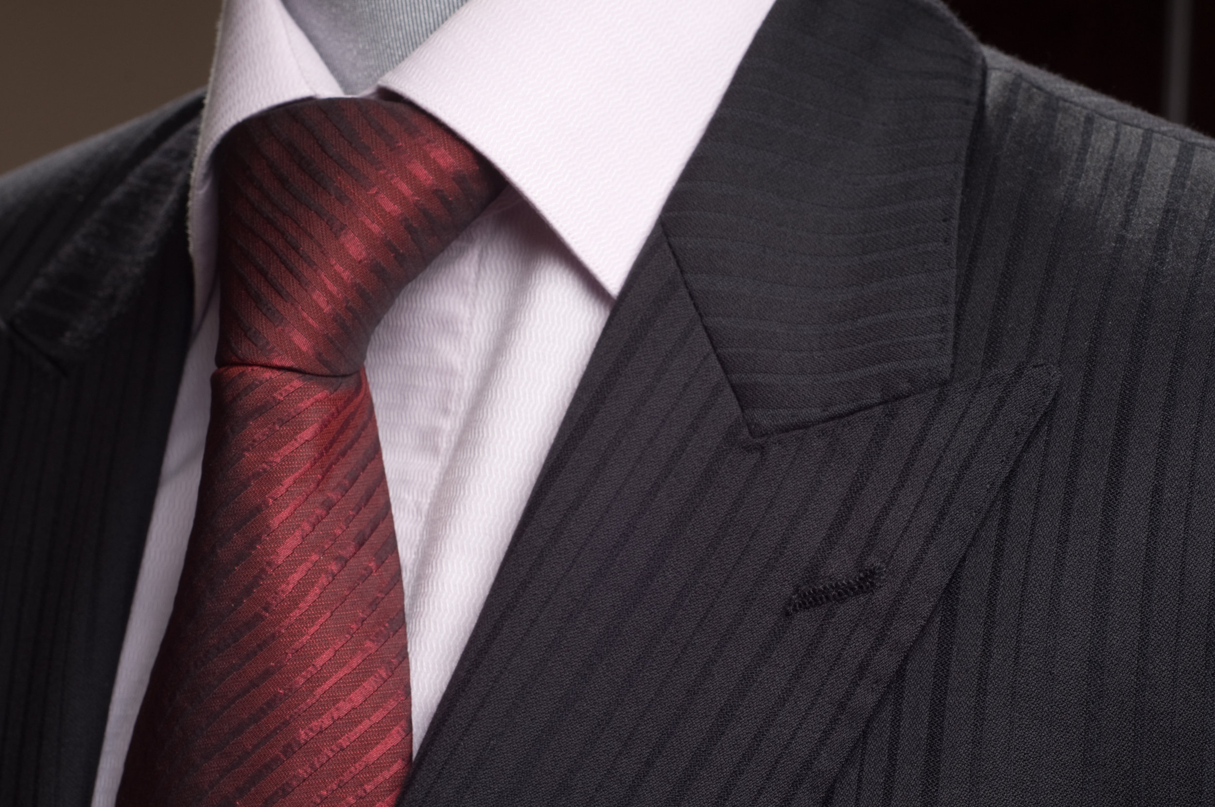 Peak lapels are known for their tips pointed toward the shoulders. They are considered to be a more formal style and are standard on, but certainly not limited to, double breasted jackets and tuxedos. They are now common in business formal wear as well. Peak lapels can add to the illusion of broader shoulders and increased height. Their lengthening effect often results in a slimmer look. The lapel width is determined by a variety of factors and usually depends on current trends. Traditionally, however, the lapel extends for about half the shoulder width. Ultimately, a proper, tailored fit customized to your proportions is the best way to guarantee a dapper and timeless look.