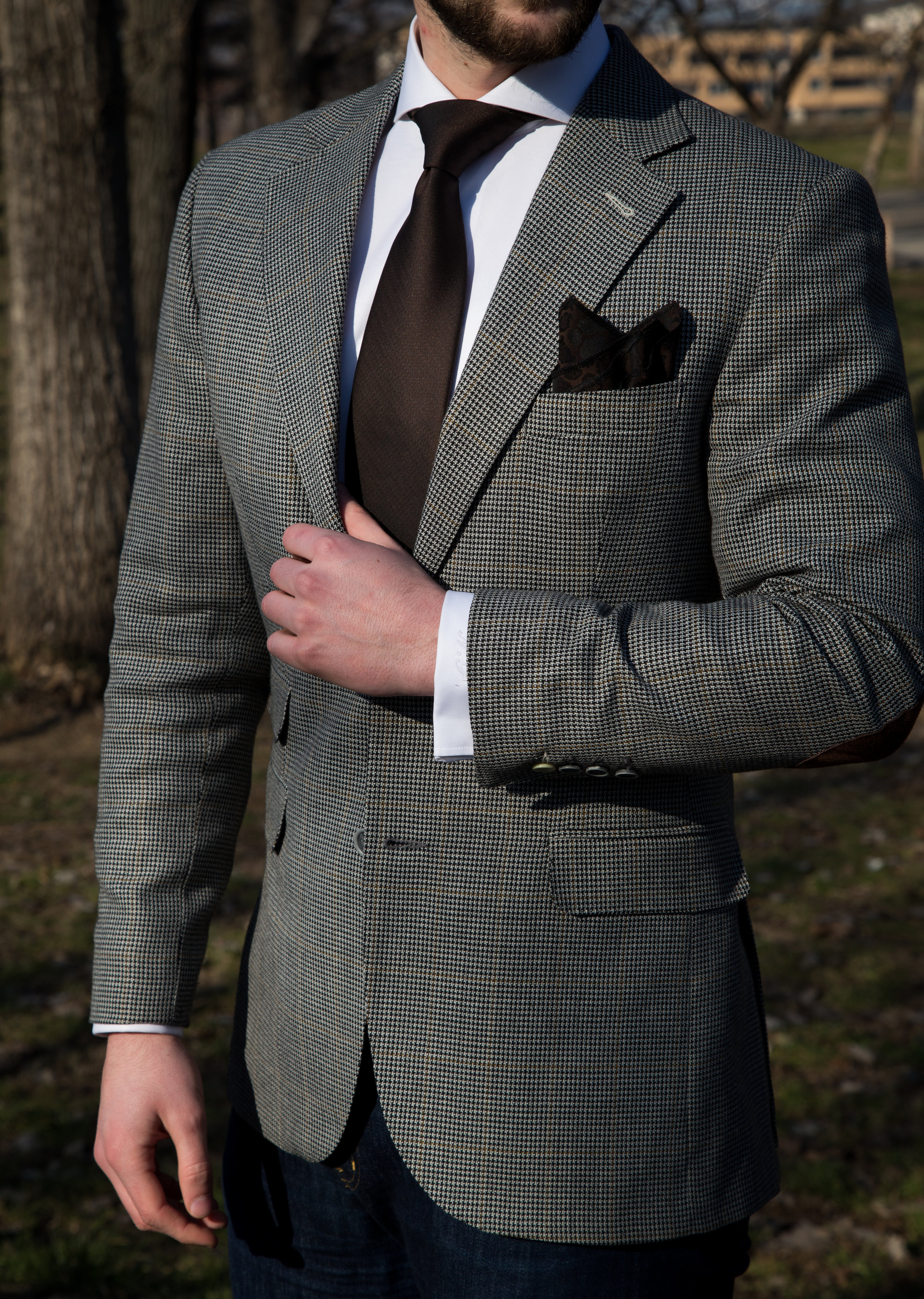 "- 6. The cuffs of your sleeves should peek out of the jacket sleeves by half an inch. Avoid the jacket sleeve hitting your knuckles at all costs!7. The edge of your suit pants should just brush the top of your shoes, though if you want to show some sock have it cut right above the ankle. Just make sure you don't have extra length as it creates a sloppy appearance and a smaller stature.8. The suit jacket length will help dictate how ""balanced"" your upper body is to your lower body. Mess up the length of the jacket and the whole suit will look off. If you are under 5'9"", the jacket should end right around the mid crotch area. Any taller should be in the mid to lower range.9. Suit pants should fit perfectly around your waist with no need for a belt to hold them up. Unlike jeans, which are generally designed to sit lower, suit pants should hit near the high hipbone area, or even slightly higher.10. Most suit jackets are made with a standard, or ""democratic"