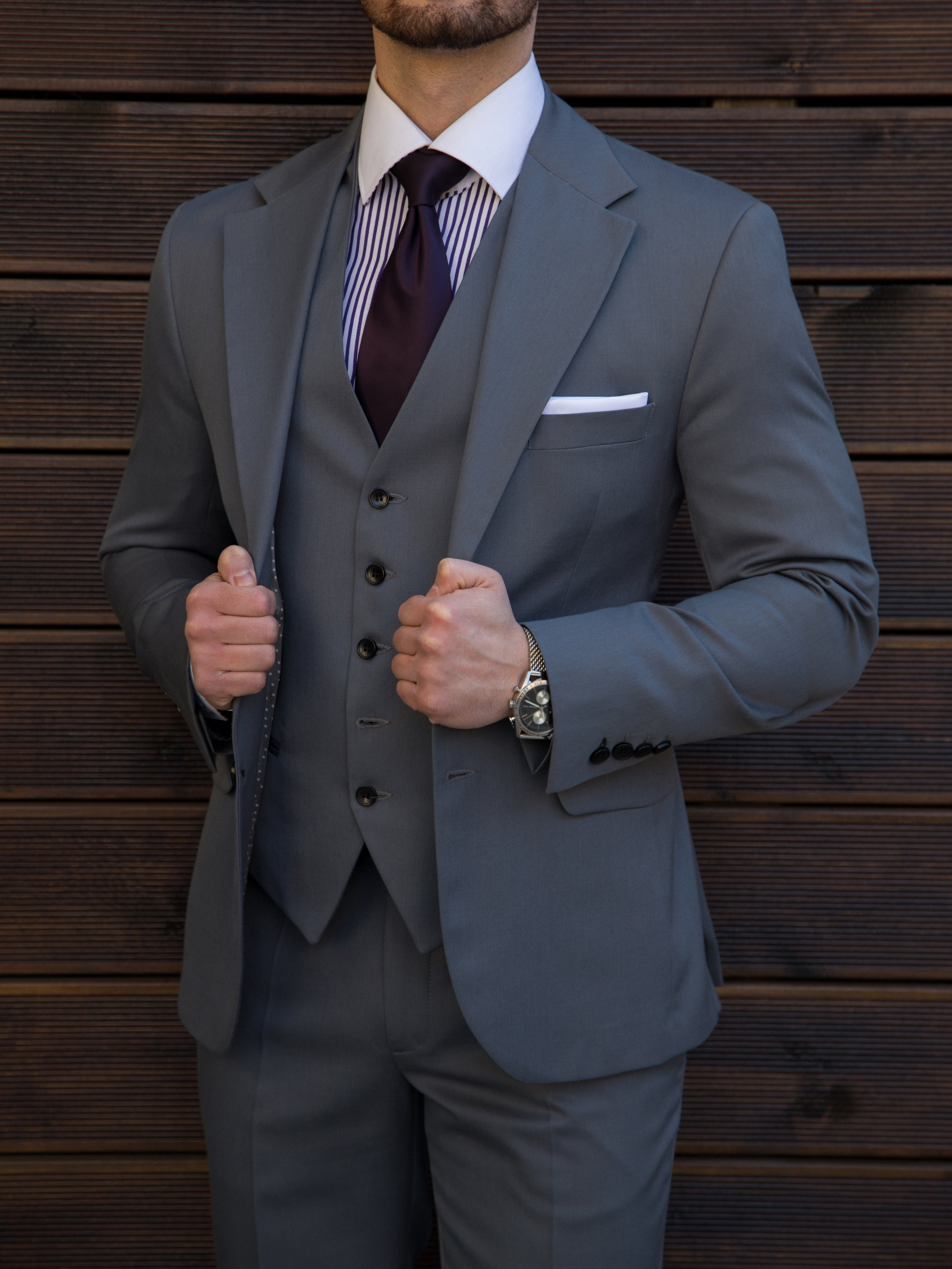 - 11. Choose a fabric according to how often you'll wear the suit. The most versatile option is a soft, but durable wool like super 120 (a measure of yarn fineness; higher than 120 is generally too delicate for daily use).12. When it comes to wearing an undershirt, be sure to avoid letting it peak through in any way as it cheapens the overall look no matter how well everything fits. With many deep neck options available, pull for those with any open collar look.13. Vests are not only a practical touch for colder climates, but also adds a formal touch that can set you apart. It is best worn with a single-breasted suit so it is actually visible. Also, you can never go wrong with a vest hat combo to really add style to your overall look.14. The collar of the jacket should rest against your shirt collar, which should in turn be resting against the back of your neck. All of these should touch lightly with no significant gaps in between. A gap can mean the jacket is too loose and bunching under the back of the jack collar can mean its too tight.15. Be sure to slim the sleeves of your jacket to decrease the wrist gap and baggy wrinkles near the elbow. Most people go for the taper look only on the trousers but providing the sleeves a similar look will add to your polished look.