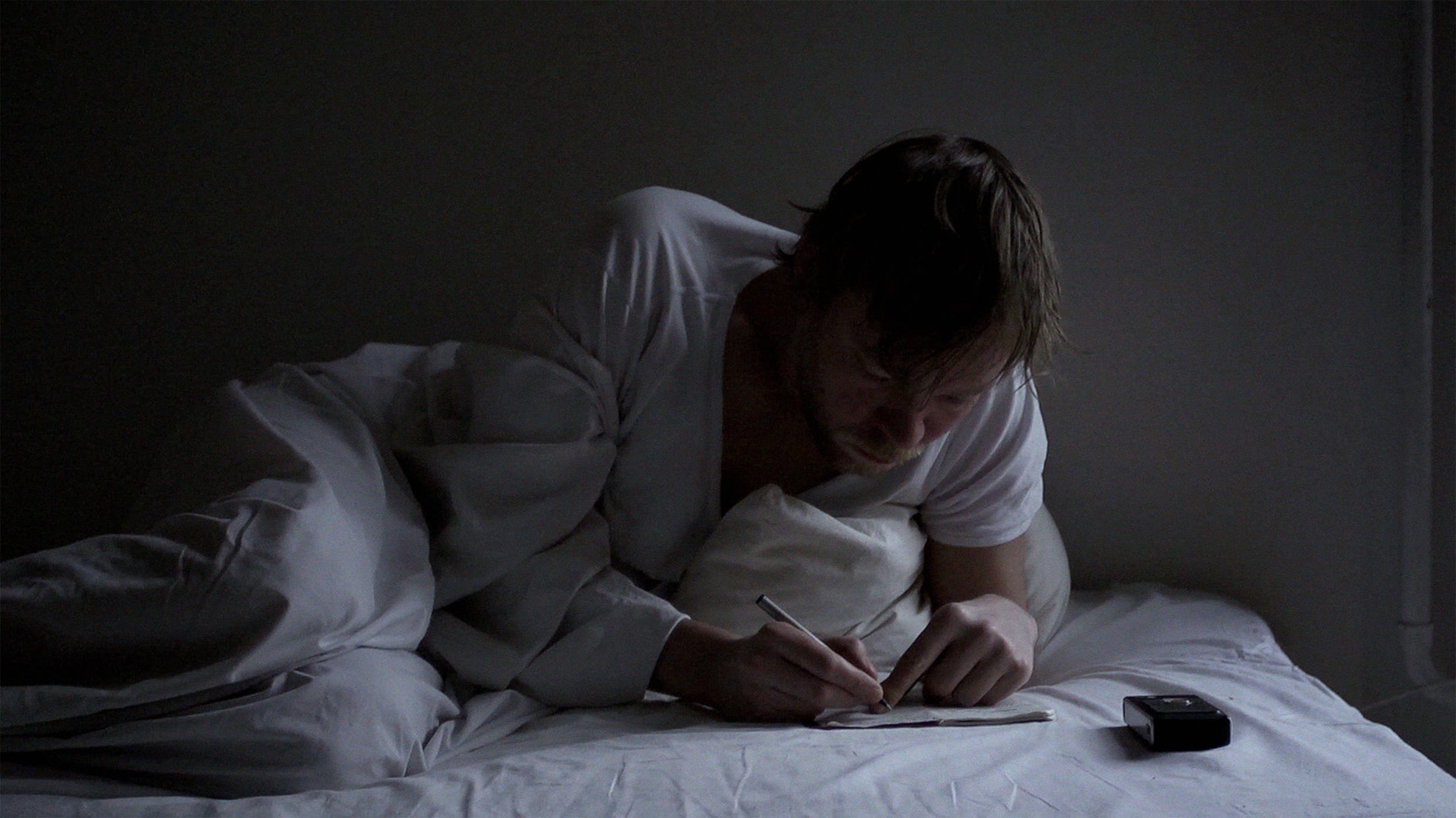 TravelingWithMrT_5-Troels_writing_in_bed_photograph_by_Simon_Lereng_Wilmont.jpg