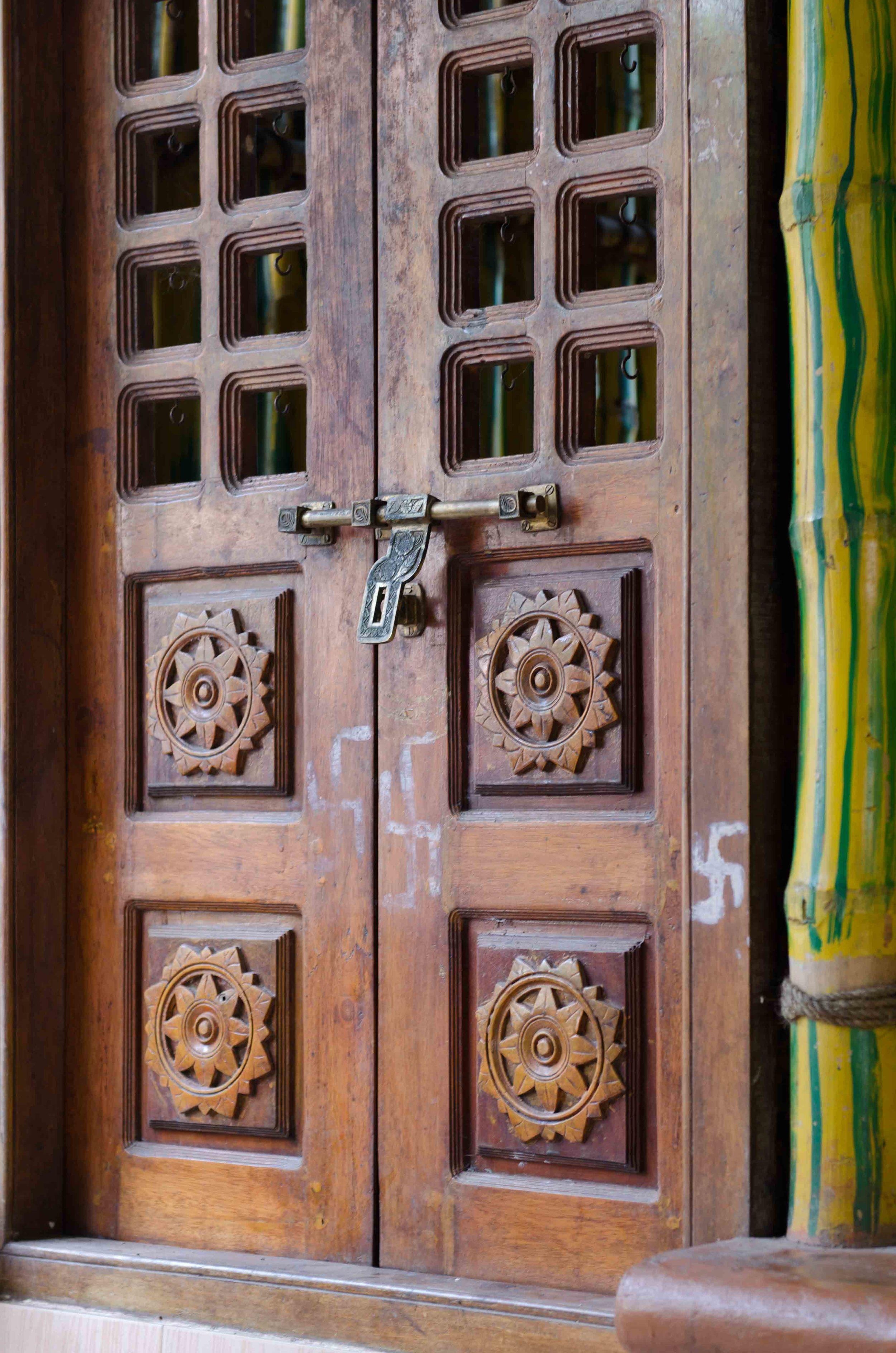 Usa de la intrarea in ashram. Svastica este simbol al pacii eterne. Sunetul OM este primul sunet de la crearea universului.