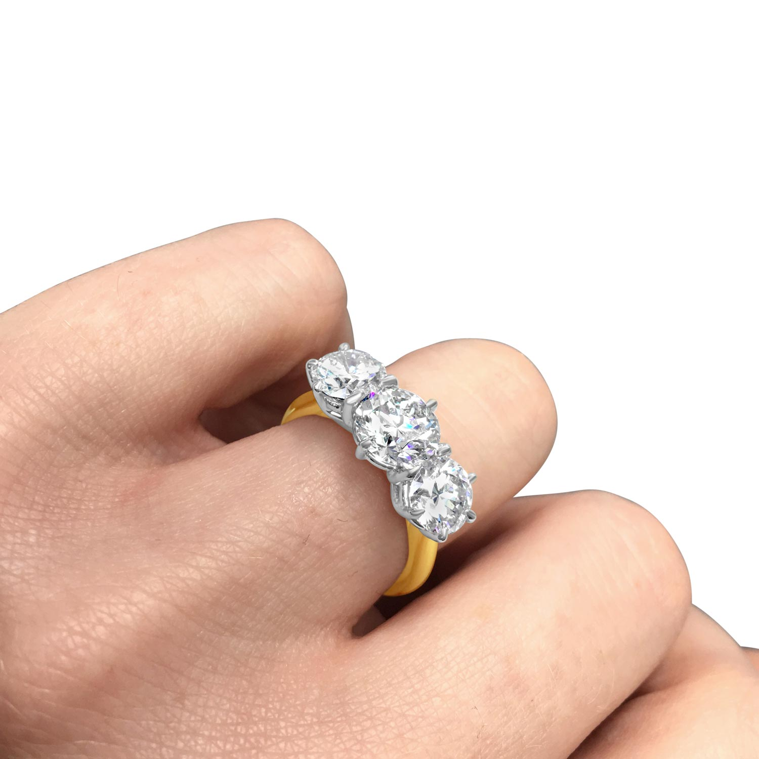 Brilliant-cut diamond three-stone claw-set ring in 18ct white and yellow gold hand