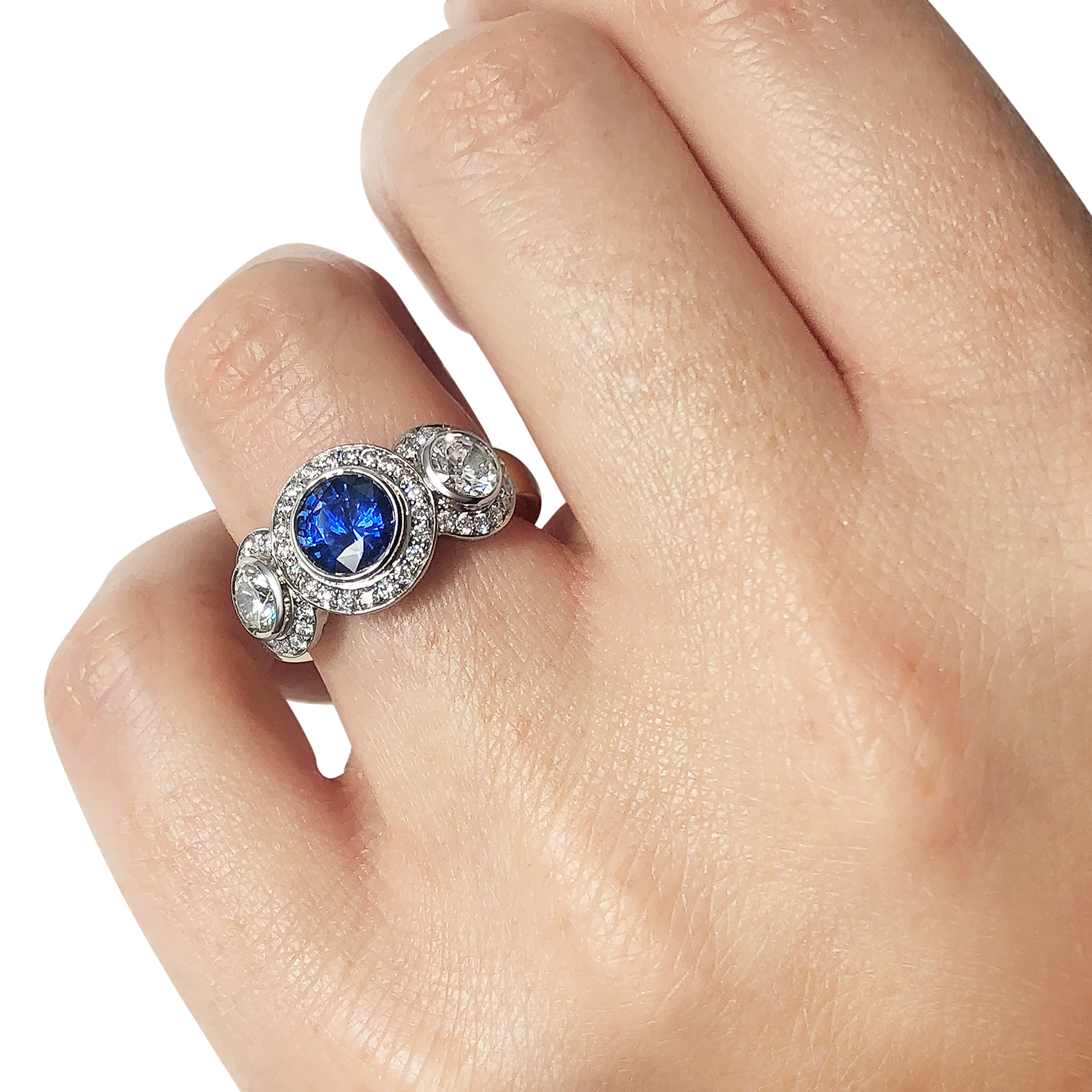 Bespoke sapphire and diamond three-stone halo ring mounted in 18ct white and yellow gold on hand