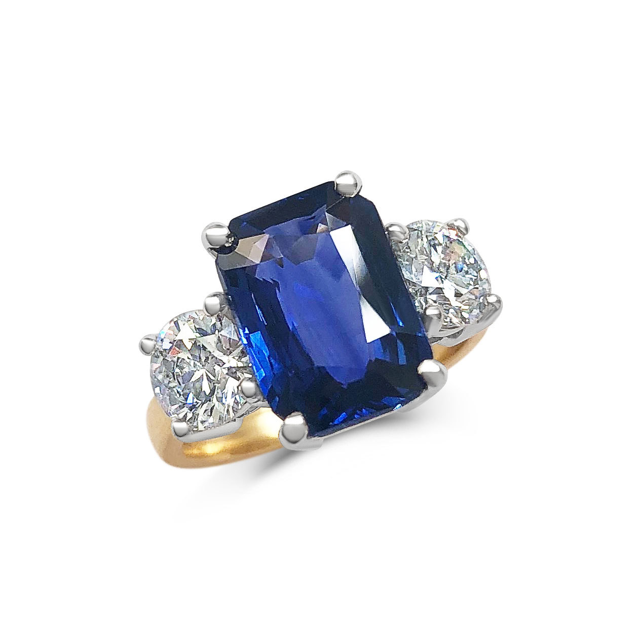 Emerald-cut Sapphire and diamond three stone ring set in 18ct yellow gold