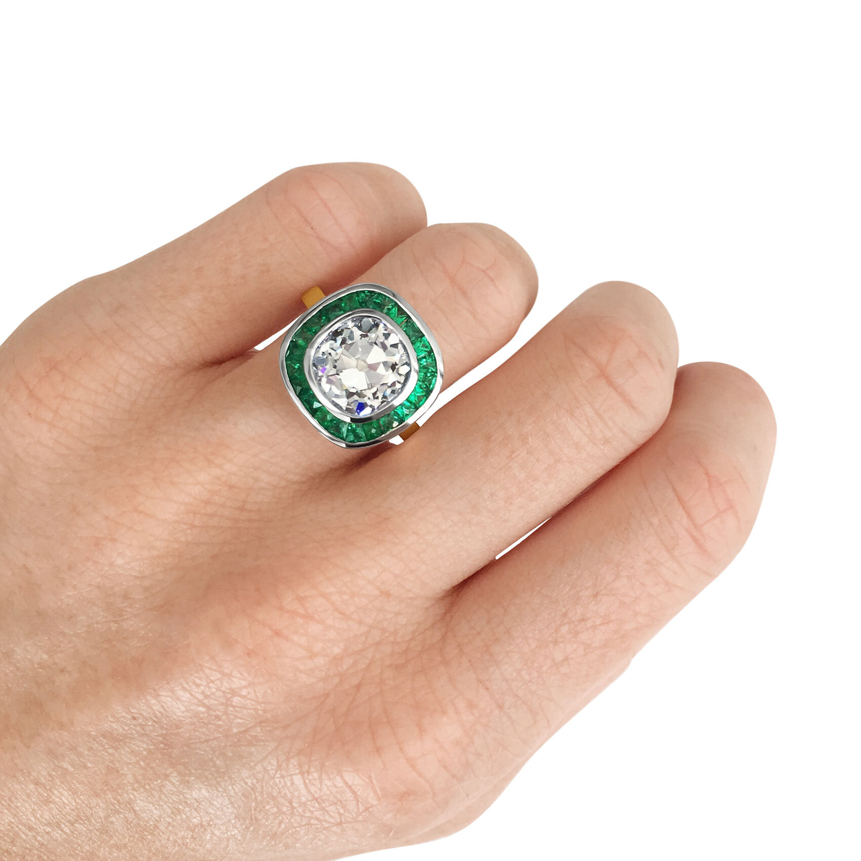 Old cut cushion-cut diamond target ring with emerald halo mounted in 18ct yellow gold.