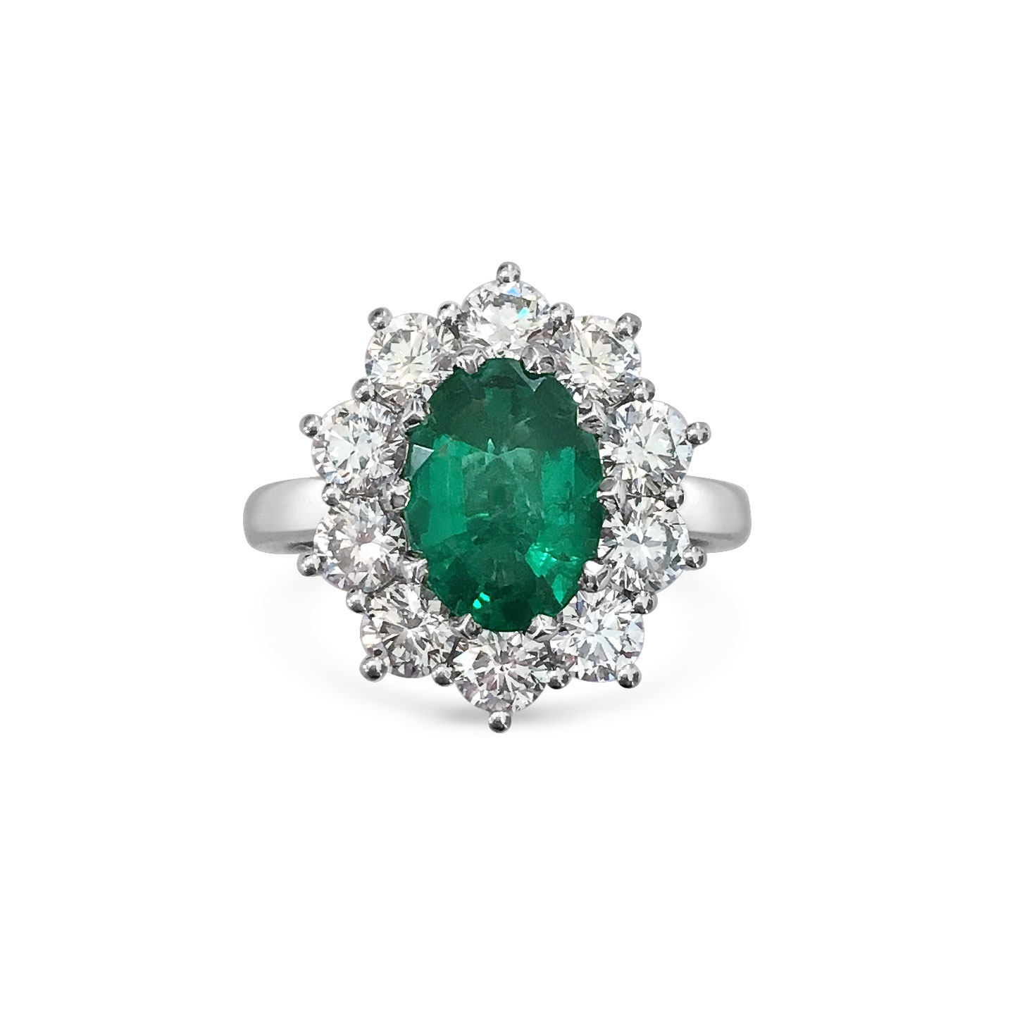 Oval emerald with diamond halo engagement ring, mounted in platinum.