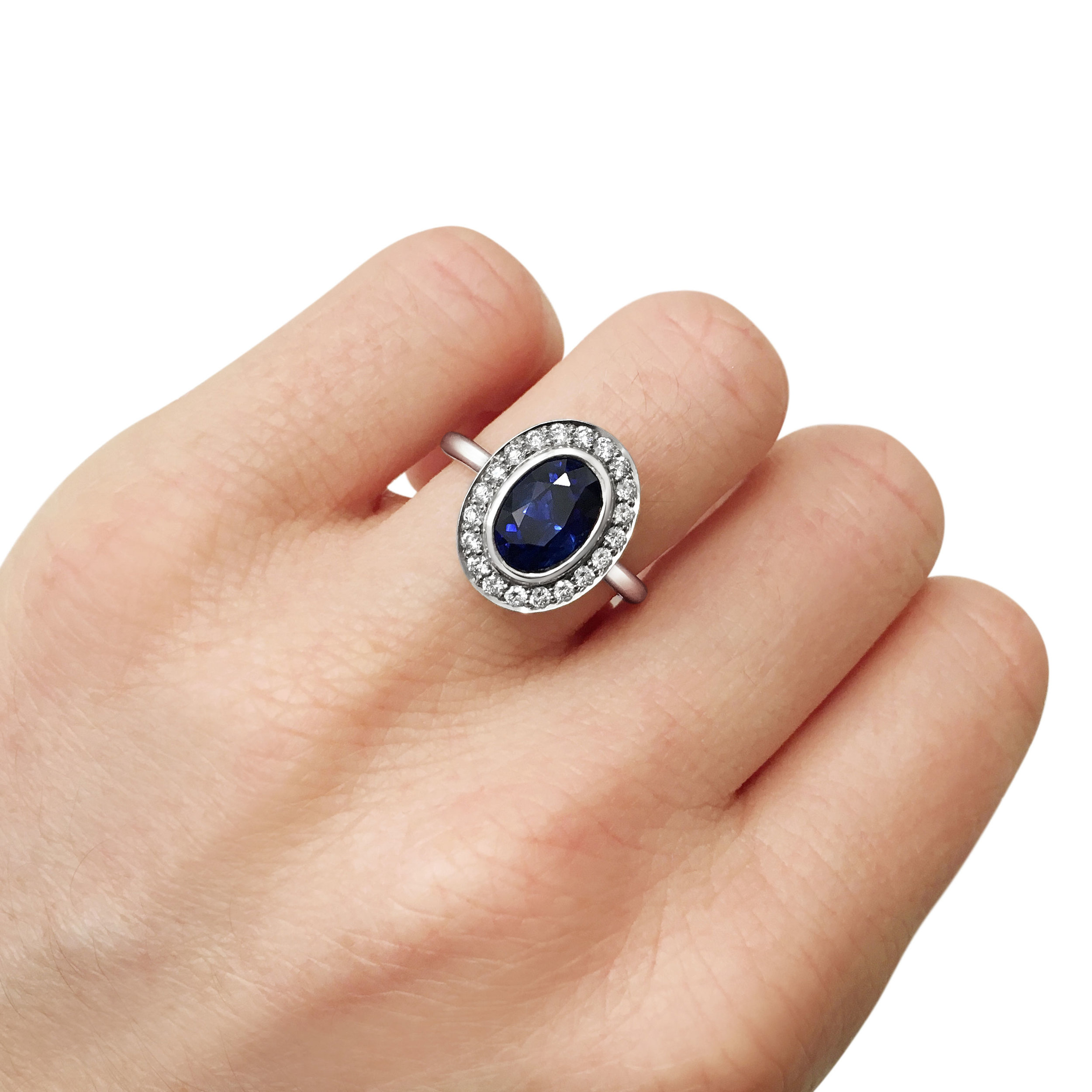 Oval sapphire with diamond halo engagement ring, mounted in platinum.