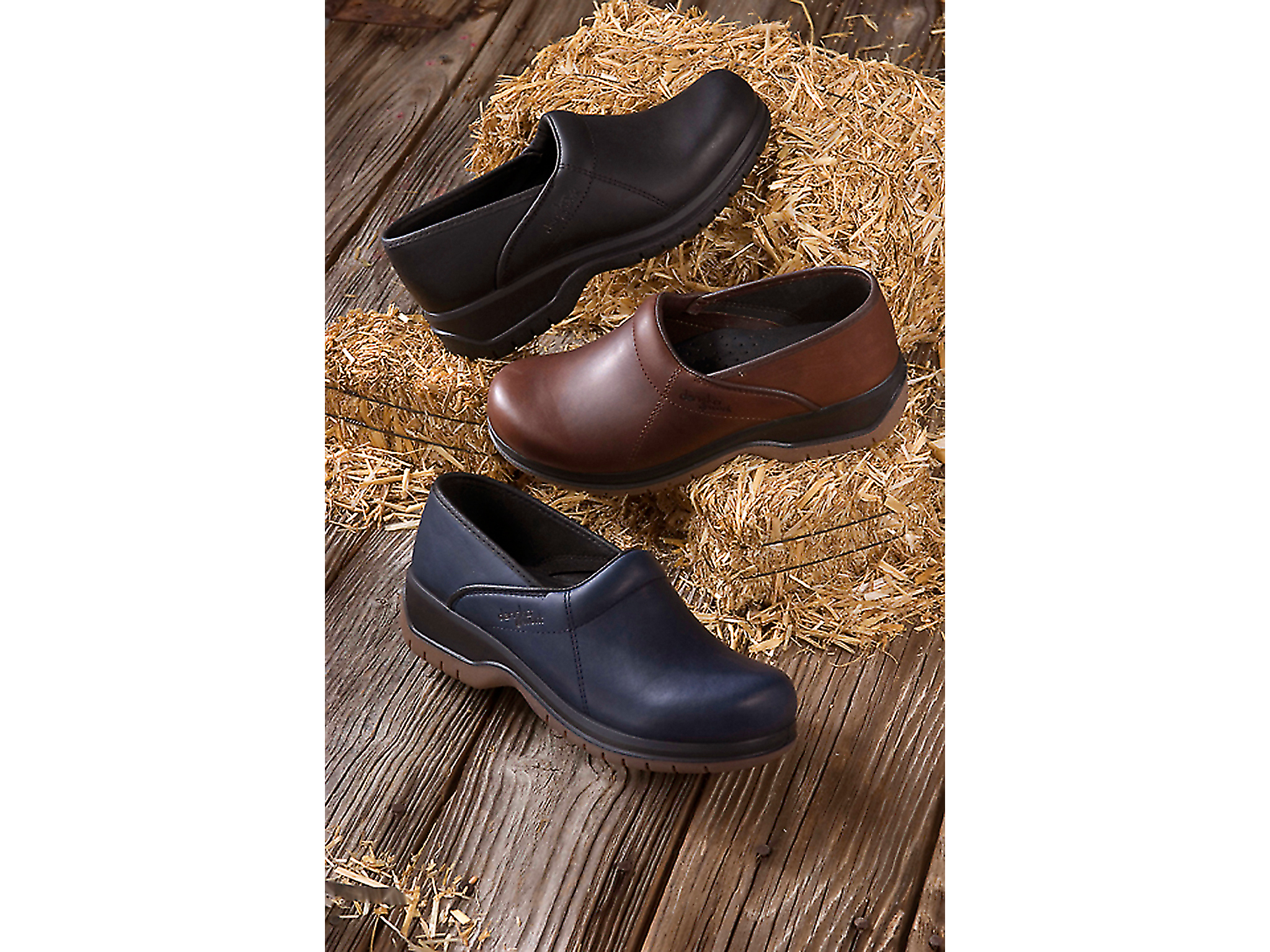 Product shot for catalog of clogs with hay and old wood by photographer Craig Anderson