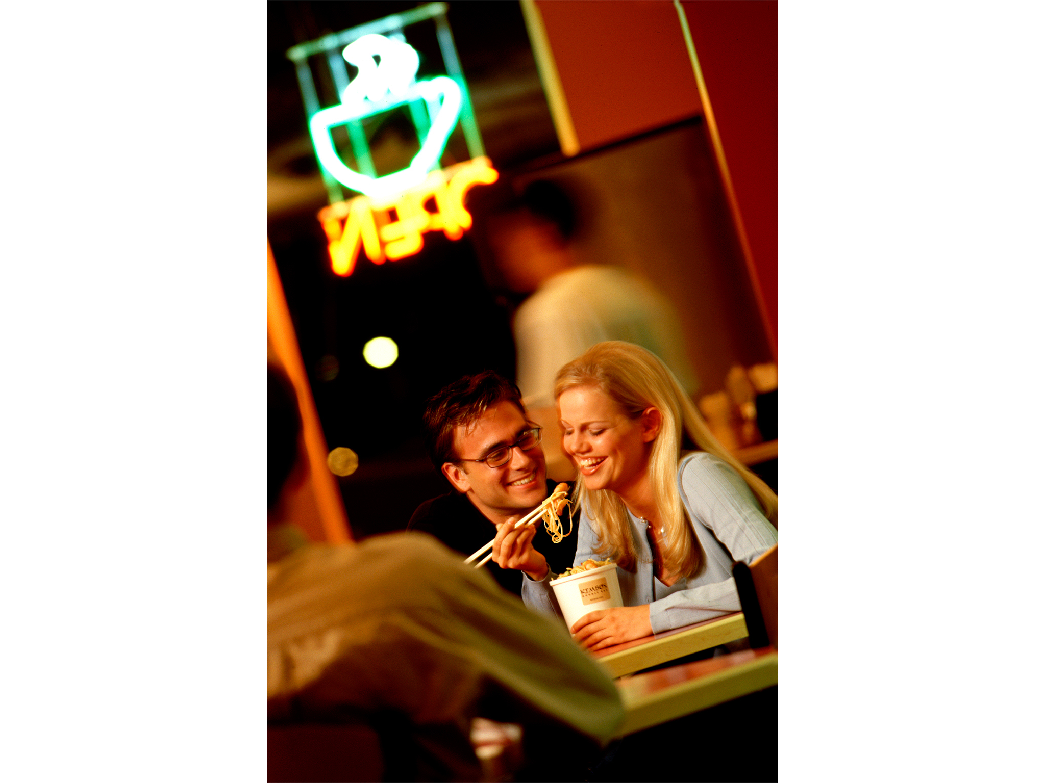 Couple eating noodles with neon sign