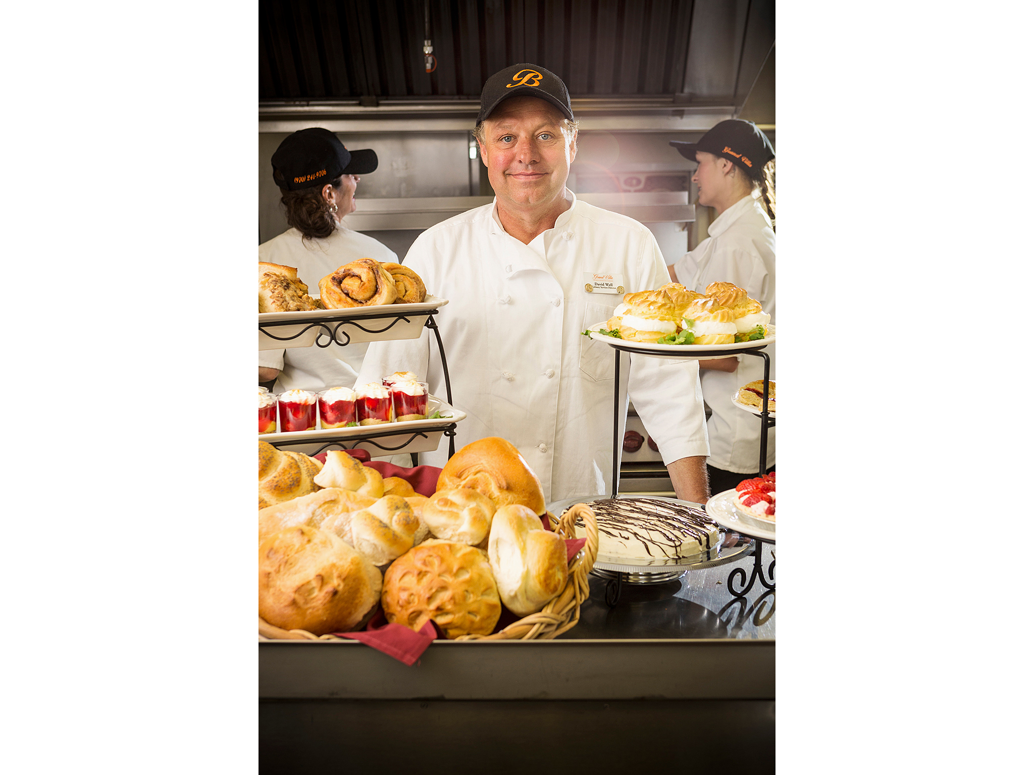Pastry chef in kitchen with pastries on display