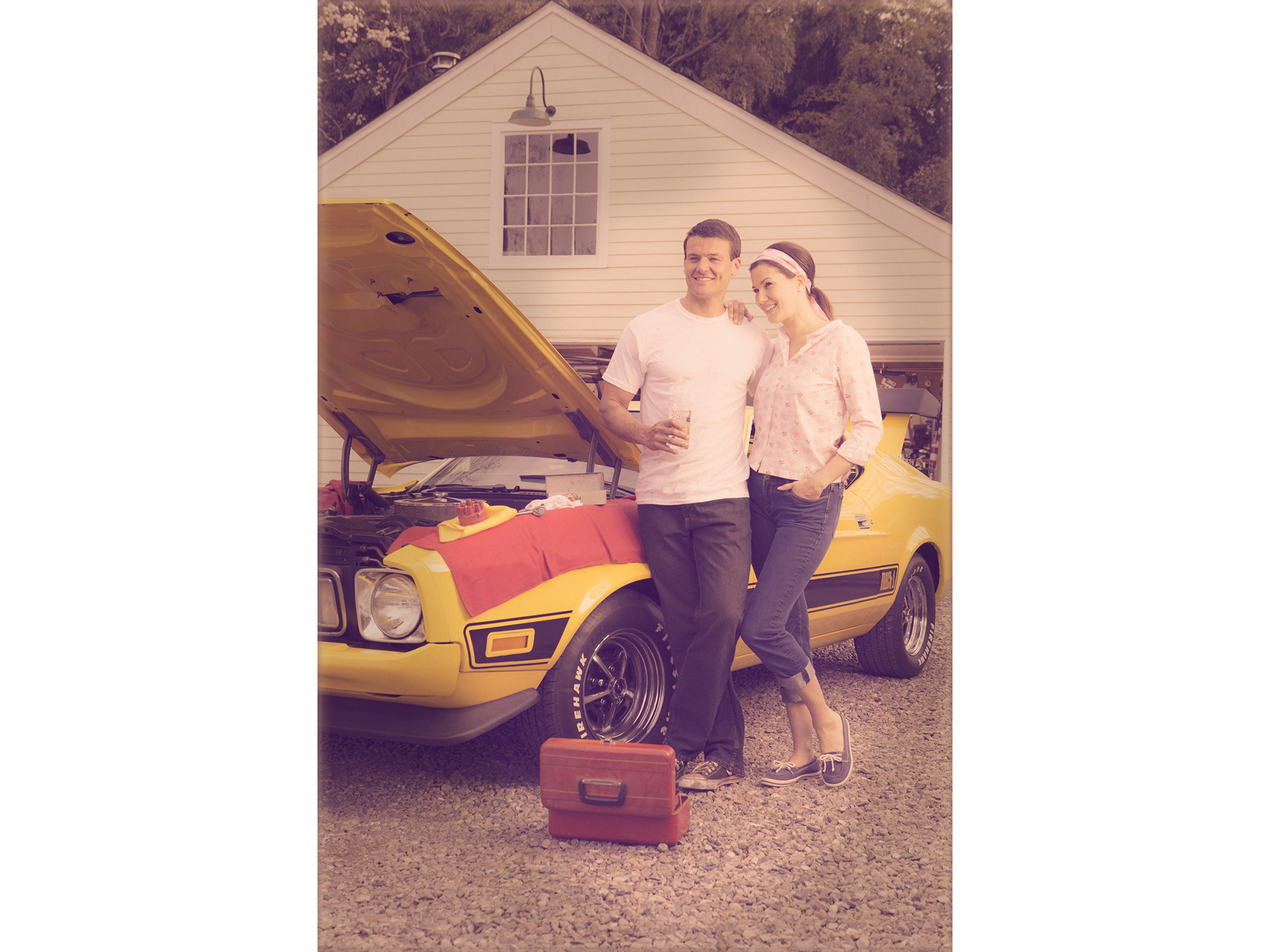Retro photo of young couple working on yellow Ford Mustang
