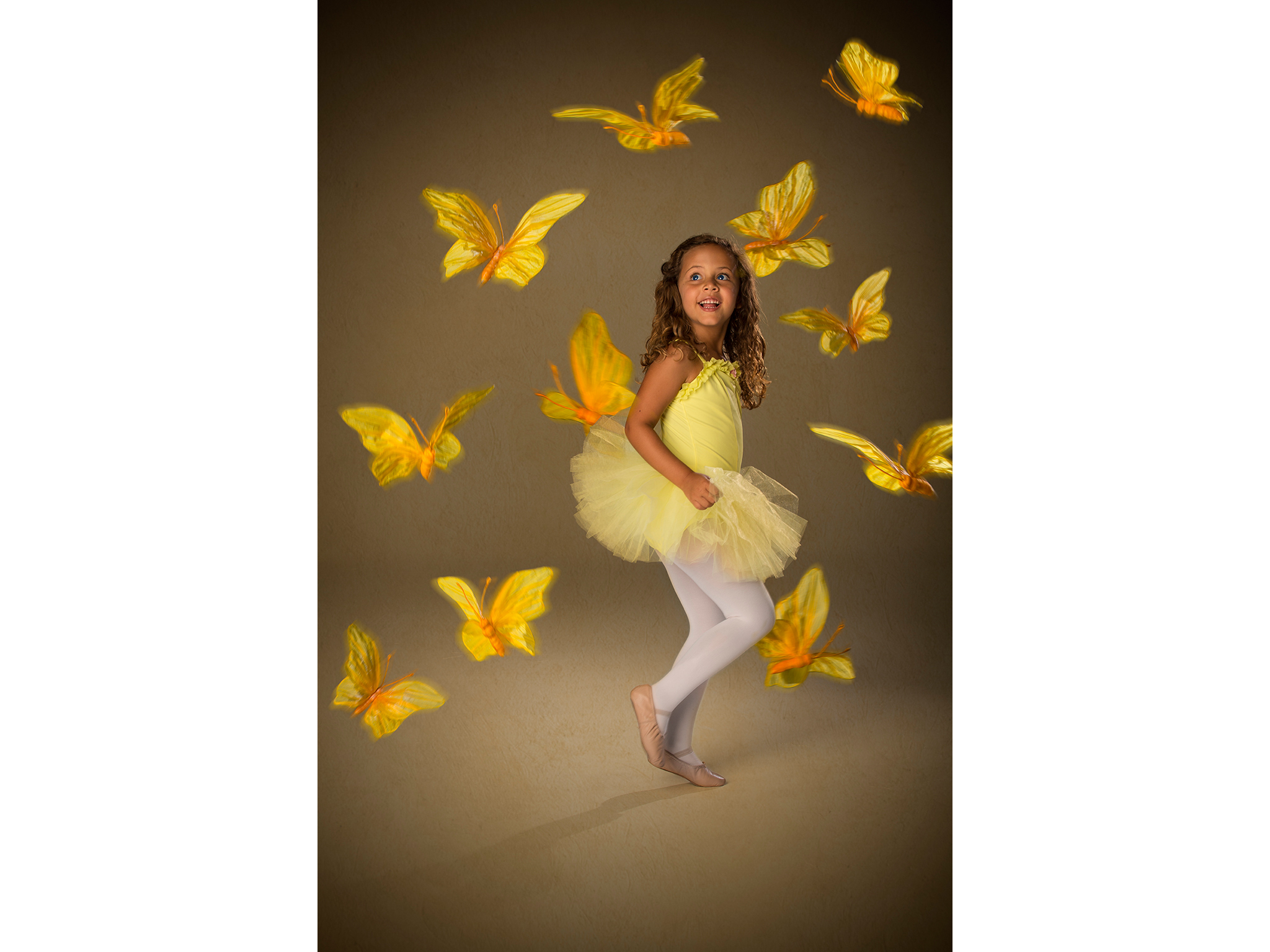 Young ballerina girl in yellow with floating butterflies