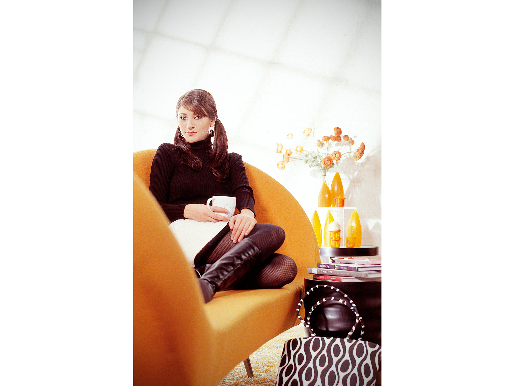 Woman drinking coffee on modern orange couch for coffee maker ad