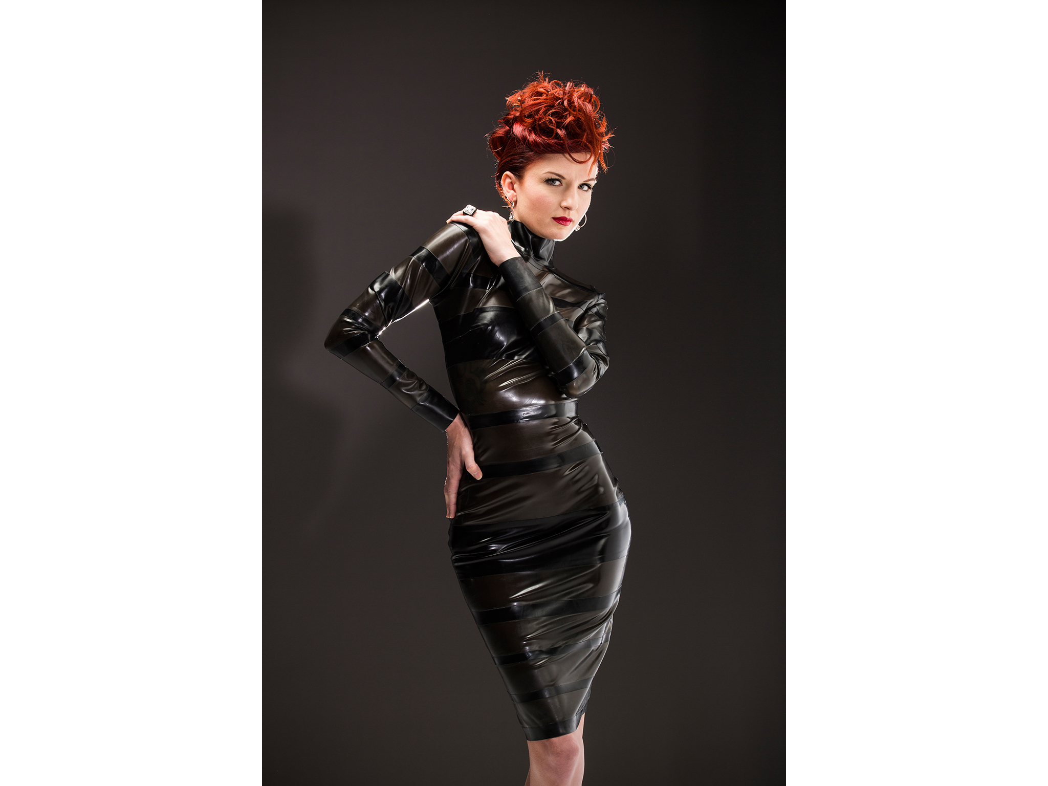 Red-headed woman in black latex dress for a fashion shoot