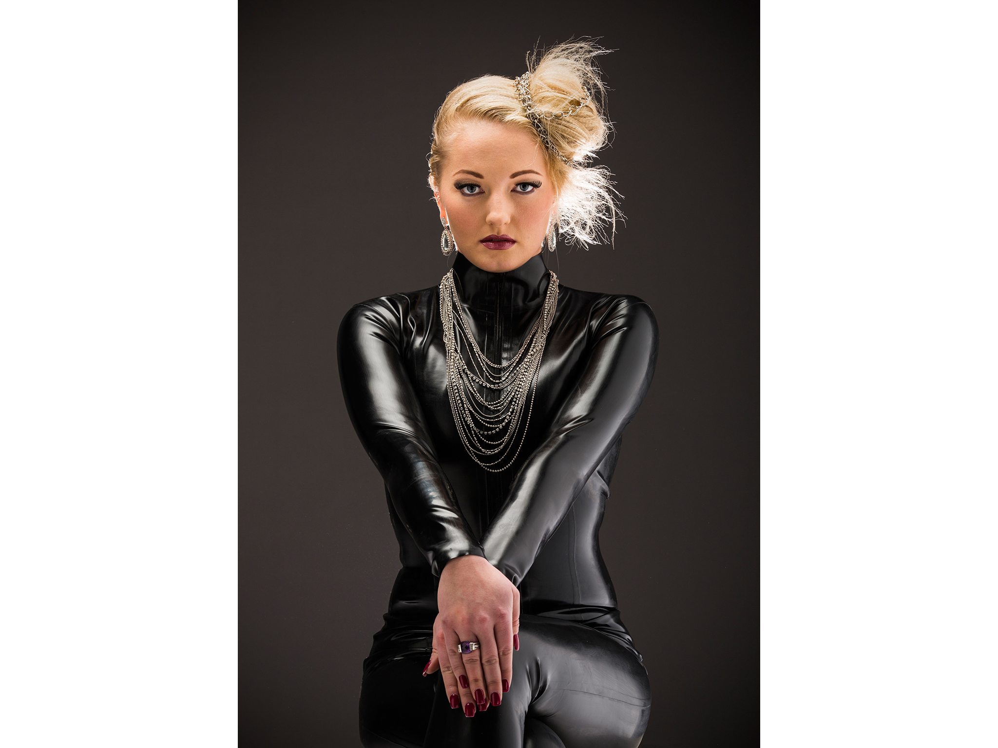 Fashion shoot of blonde woman in black latex jumpsuit
