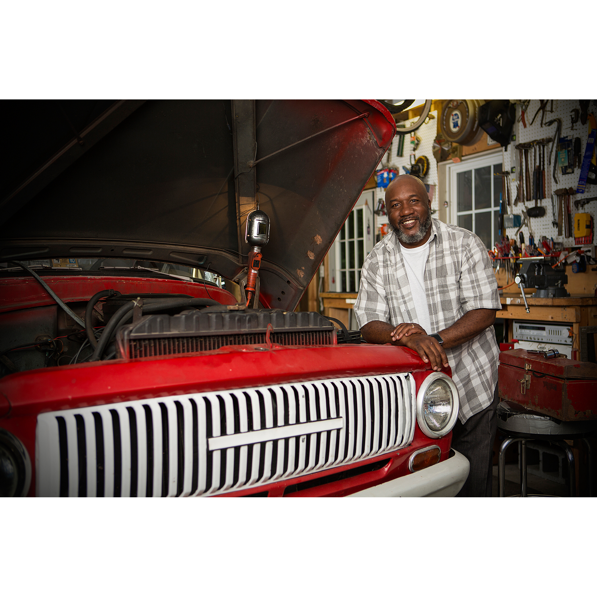 Portrait of DIY mechanic man working on old red truck in garage for billboard ad