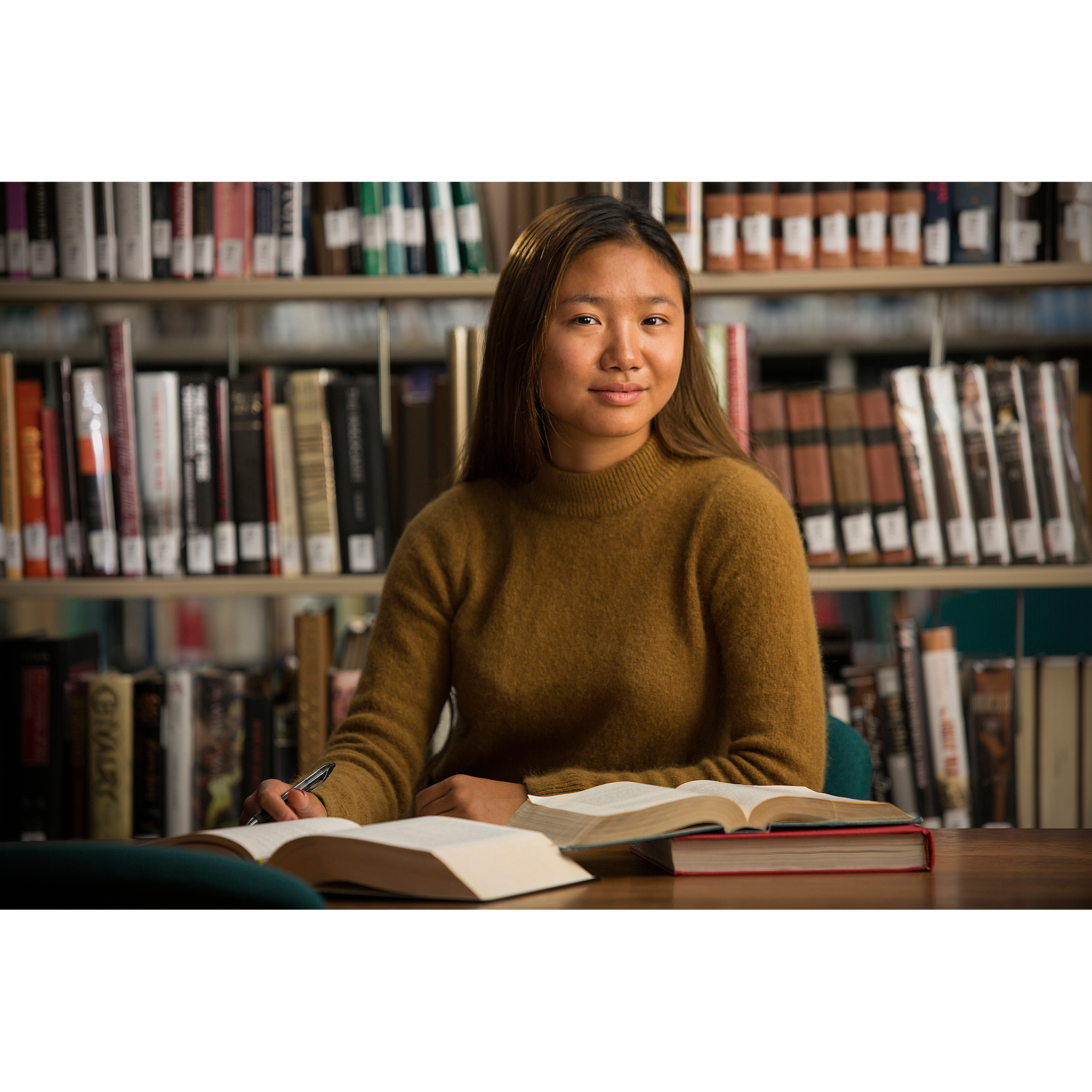Female high school student with open books studying in library