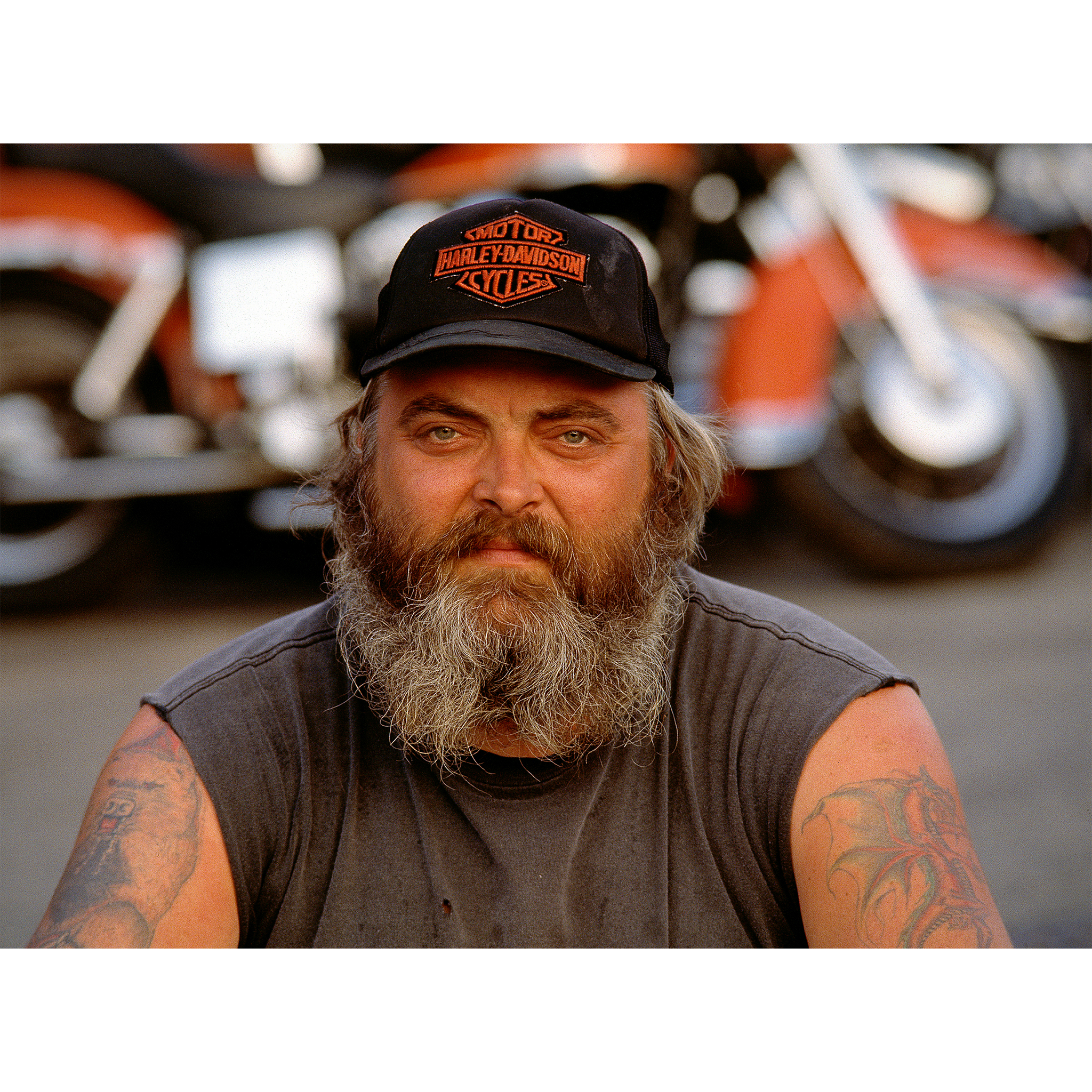 Man in Harley-Davidson hat with tattoos and motorcycle in background