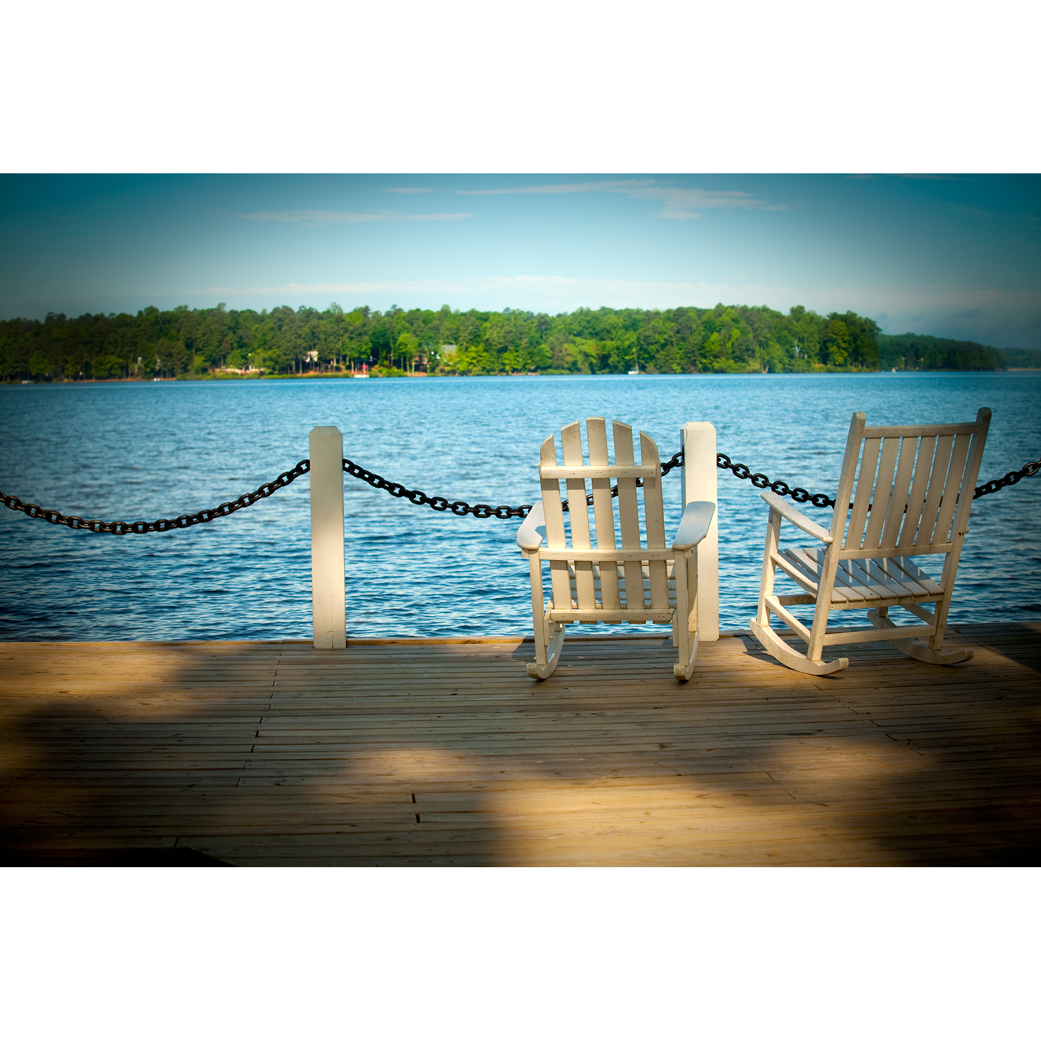 Editorial photograph of rocking chairs overlooking water