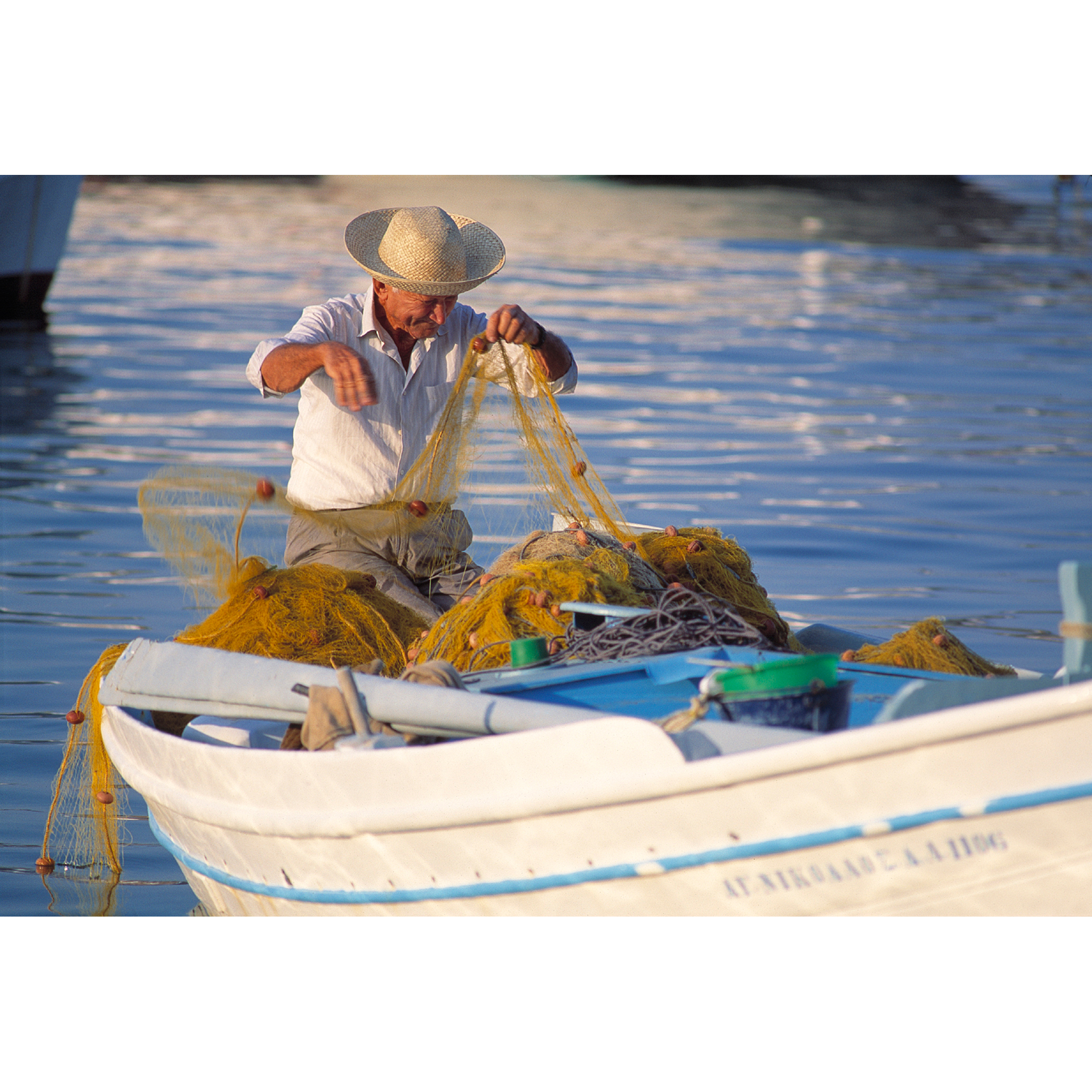 Photograph of a Greek fisherman in fishing boat tending nets
