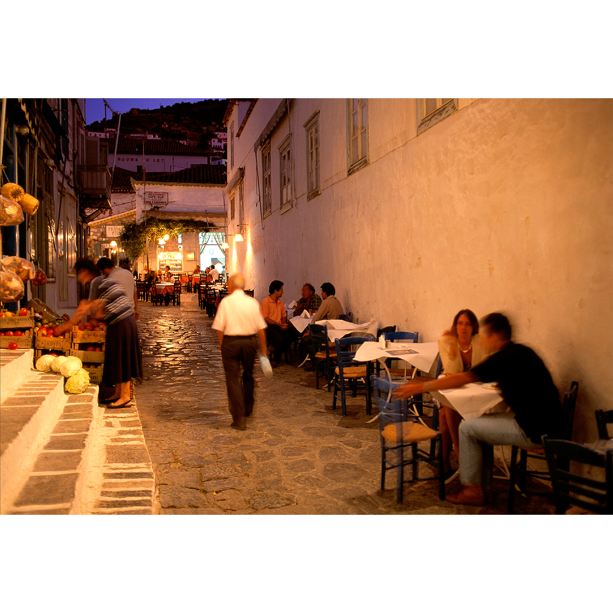 Photo of outdoor Greek restaurant at night with people eating